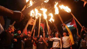 Palestiinalaiset osoittavat mieltään lippujen ja soihtujen kanssa.
