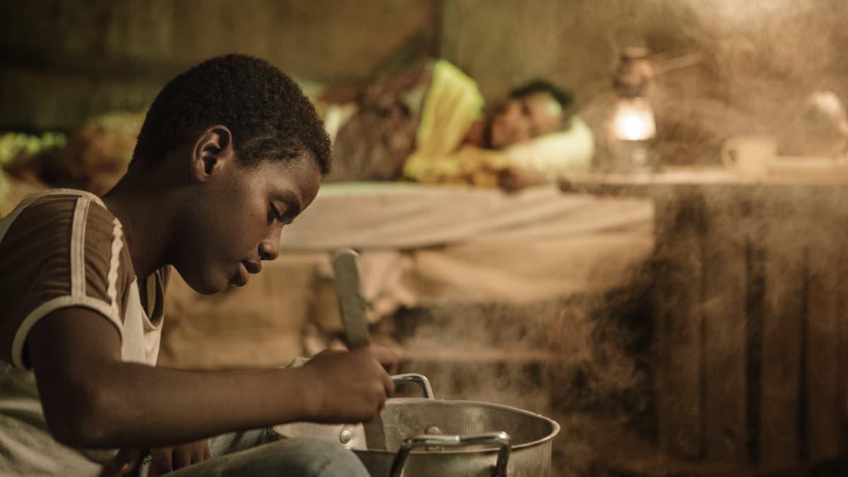 Nuori poika hämmentää jotain kattilassa. Taustalla Nasra (Yasmin Warsame) makaa sängyssä. Kuva elokuvasta Guled & Nasra.