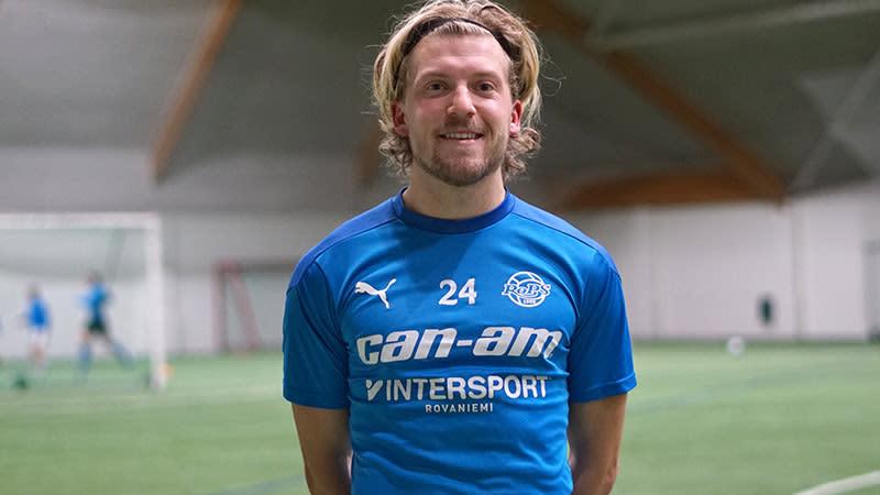 Hollantilainen jalkapalloilija Nino Roffelsen hymyilee jalkapallokentällä sinisessä paidassa kädet selän takana.