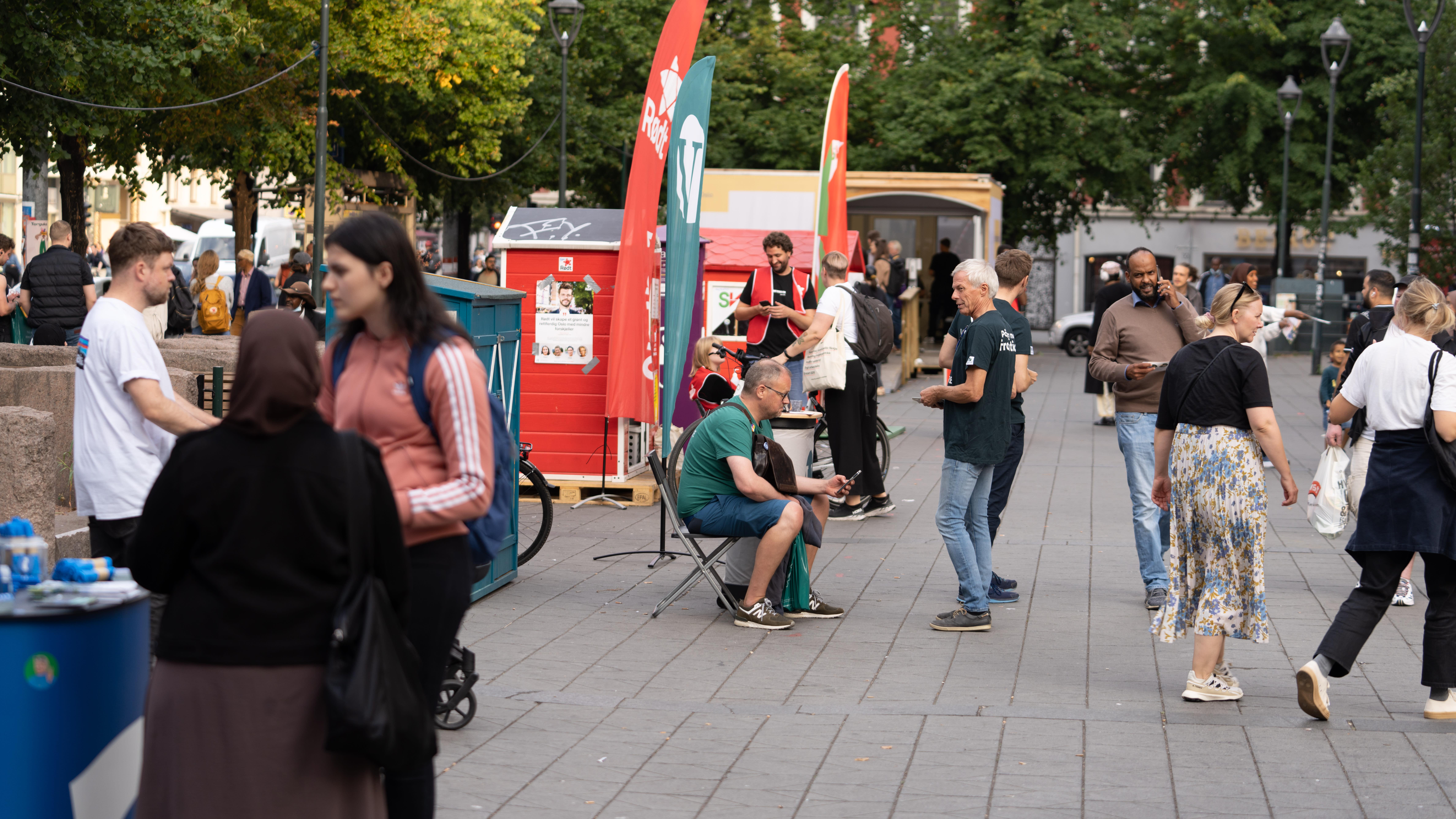 vaalikojuja kadulla, ihmisiä seisoo niiden edessä