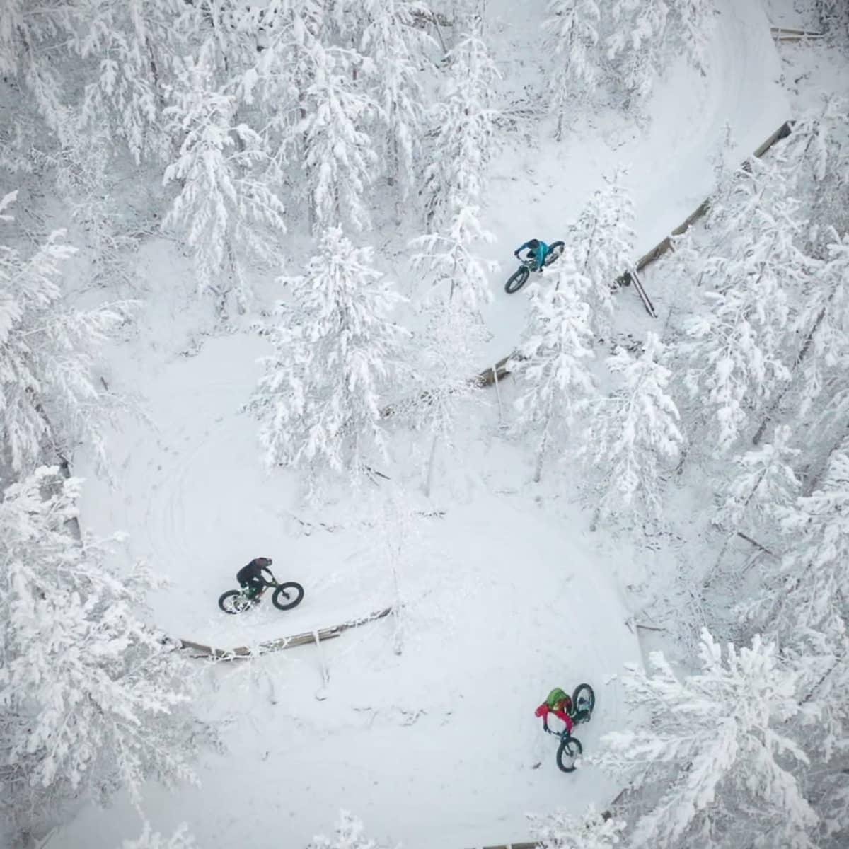 Ilmakuvassa pyöräilijöitä ajamassa alamäkireittiä lumisen metsän keskellä.