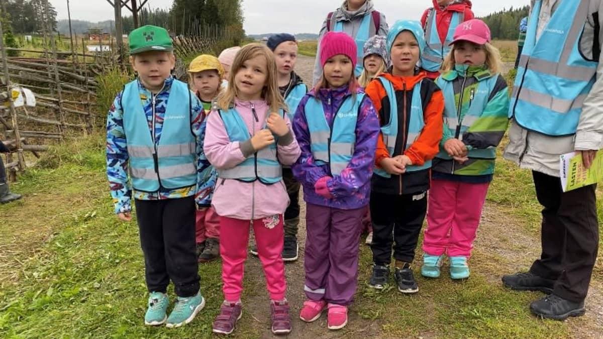 Joukko jokioislaisia esikoululaisia poseeraamassa pellon laidalla.