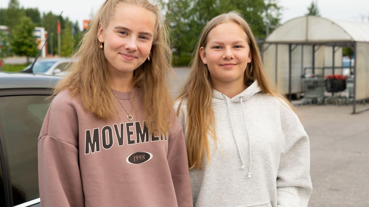 kaksi nuorta naista kaupan parkkipaikalla, pitkät hukset molemmilla, hymyilevät