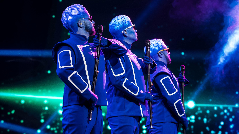Teflon Brothers seisovat rivissä lavalla avaruusasuissa ja aivoja muistuttavisas päähineissä mikkiständit kädessä, katse ulos kuvasta.