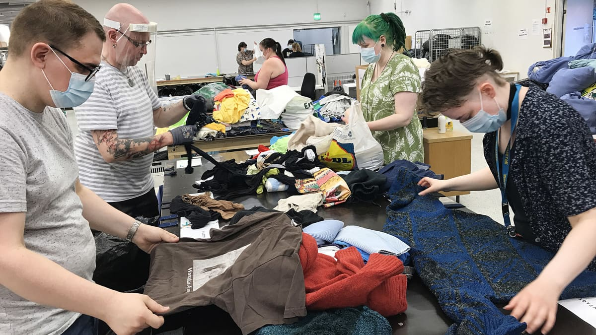 Nextiilin työntekijät lajittelevat tekstiilejä