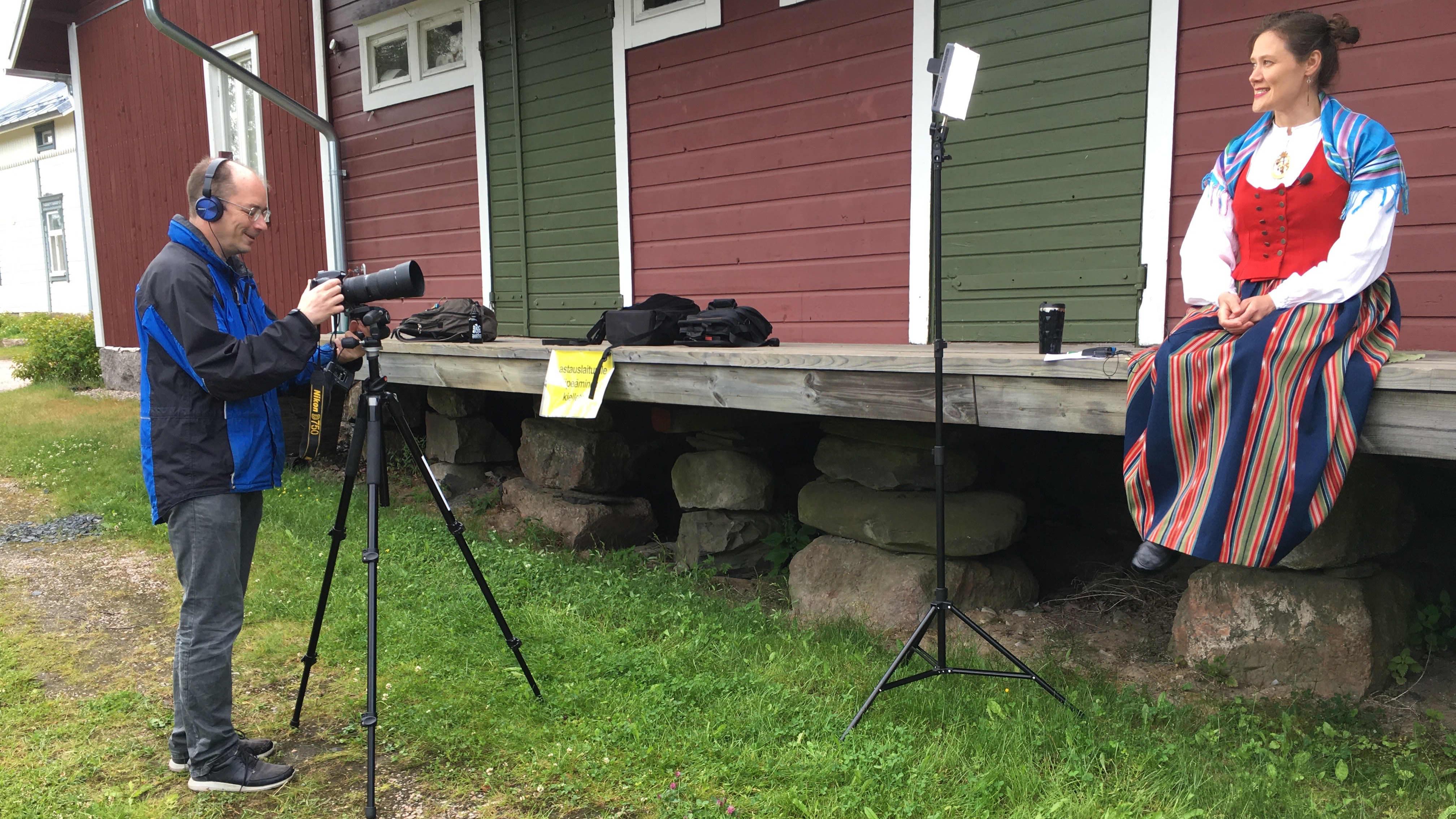 Kuvassa kuvataan VirtuaaliKaustisen aamutervehdystä. Kuvasaa näkyy kuvaaja ja kansanpuvussa oleva ohjelmajohtaja.