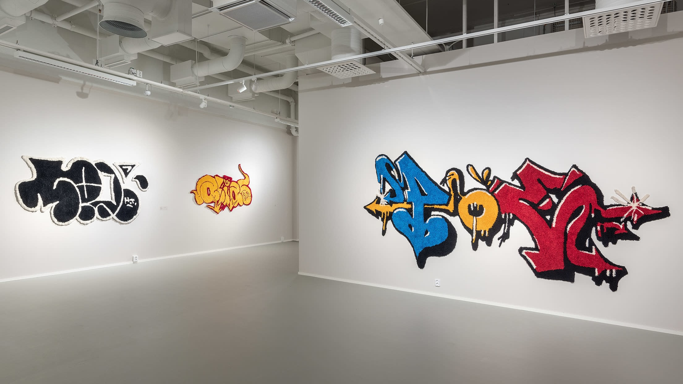 Tuftattuja, graffitia jäljitteleviä ryijyjä taidegallerian seinällä.