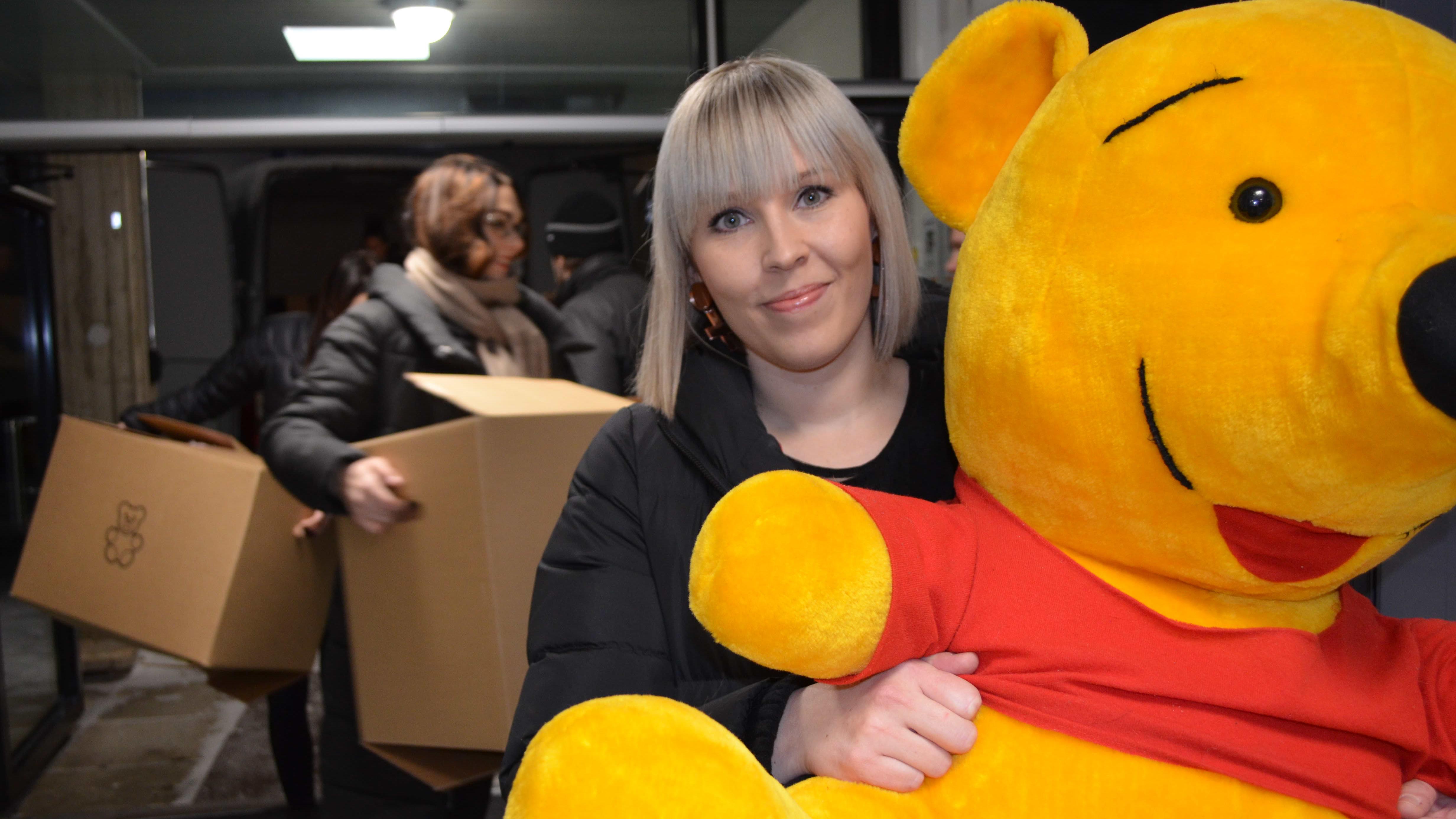 Pirjo Syrjälällä on sylissään lastenosaston pehmolelukeräykseen lahjoitettu Nalle Puh. Taka-alalla Laura Lähdesmäki kantaa lahjoituslaatikoita sisälle keskussairaalaan.