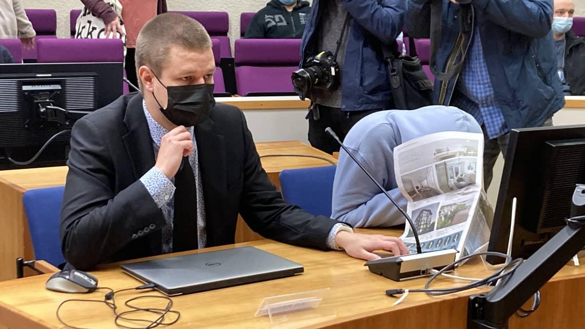 Asianajaja ja itsensä lehden taakse peittävä syytetty oikeussalissa.
