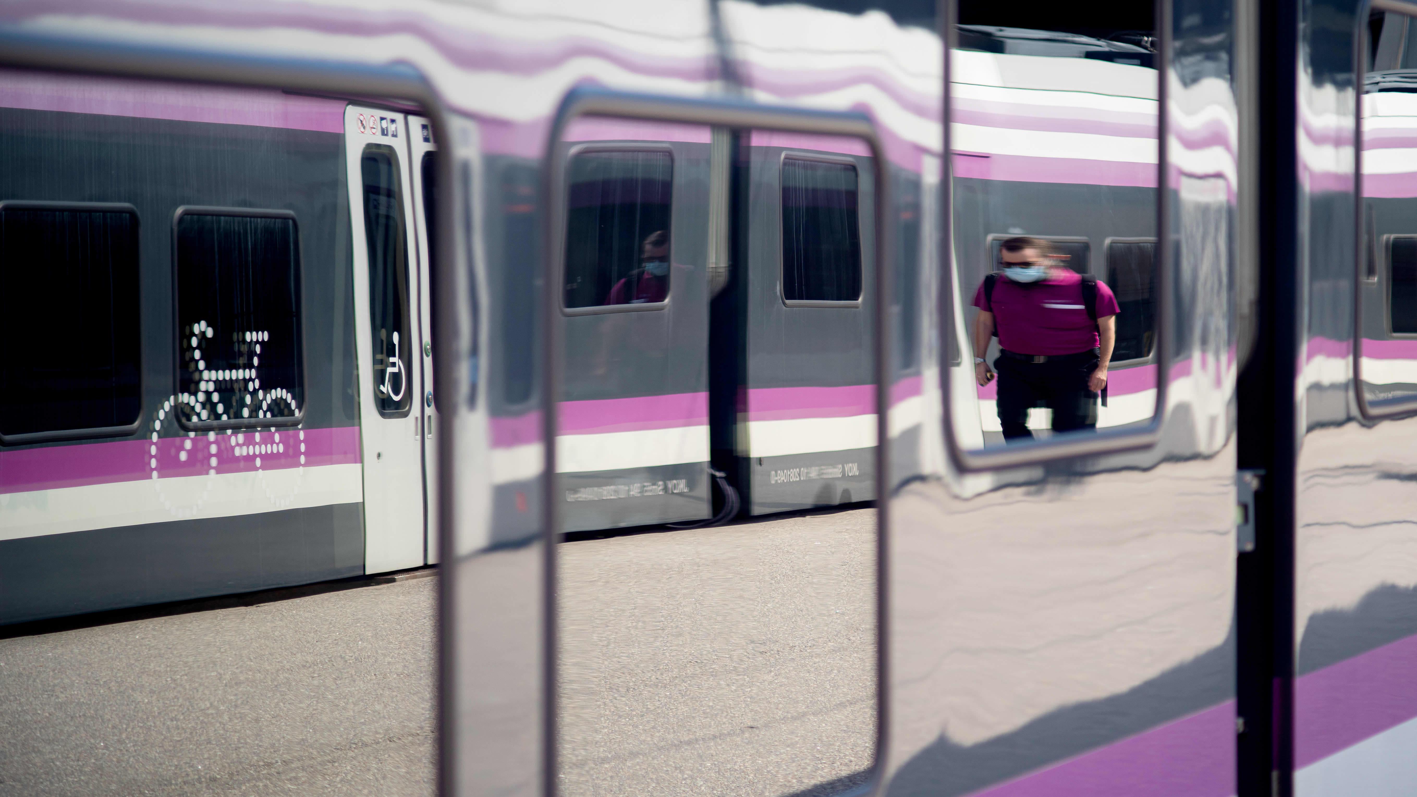 Junan ikkunasta heijastuu, kun HSL:n henkilökunnan jäsen kävelee laiturilla.