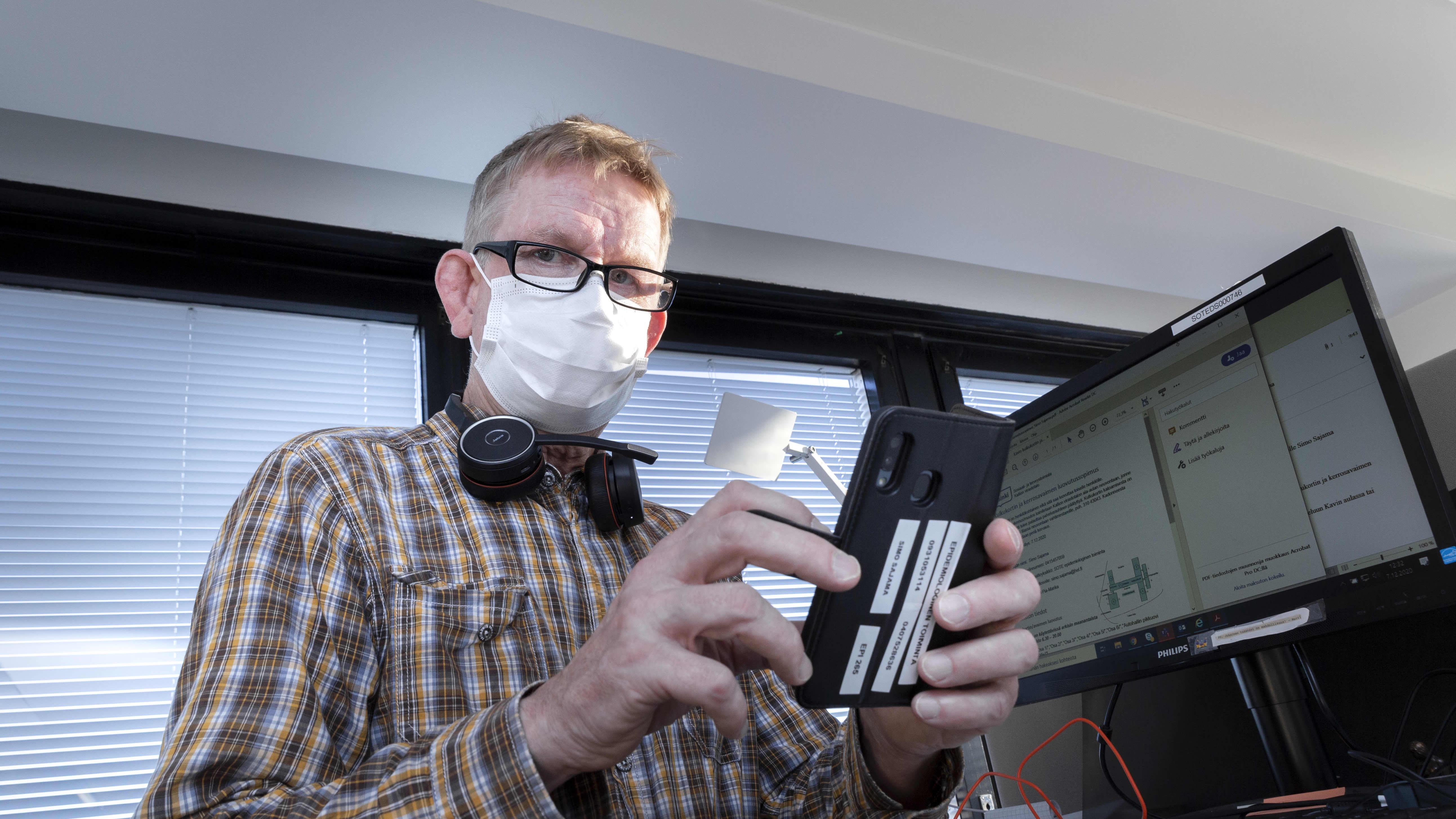 Koronajäljittäjä Simo Sajama tutkii puhelinta työpaikallaan.