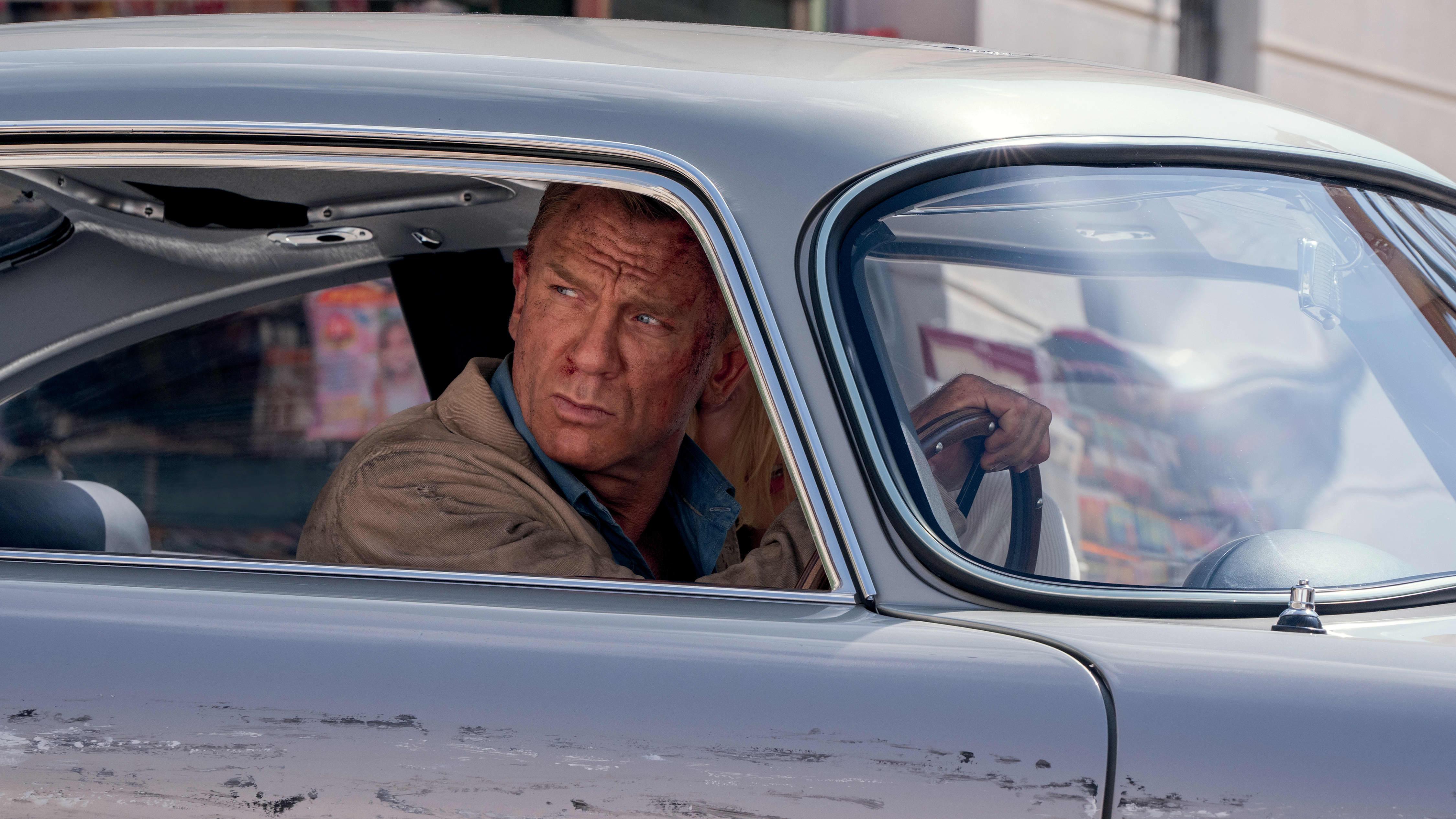 Daniel Craig naarmuuntuneessa Aston Martinissa.