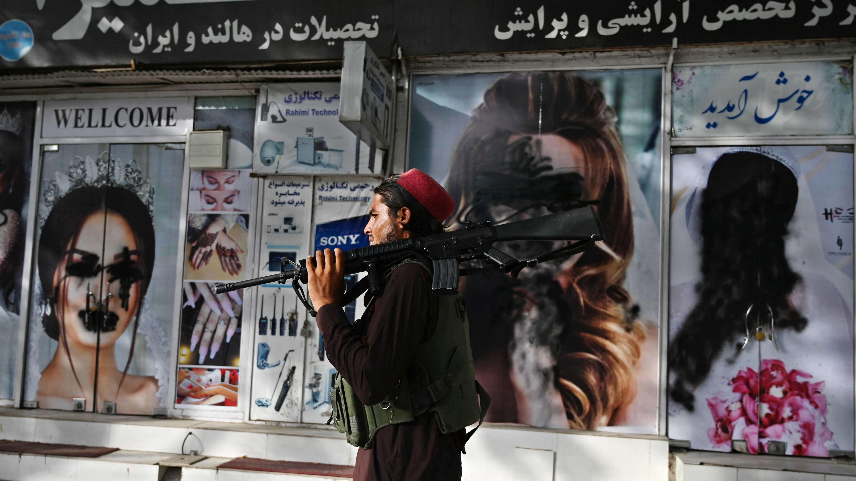 Taliban sotilas kävelee kaupan ohitse missä naisten kasvot on peitetty mustalla maalilla.