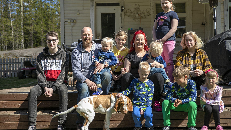 Sanna ja Juha Salin yhdeksän lapsensa kanssa yhteiskuvassa talonsa terassin rappusilla.