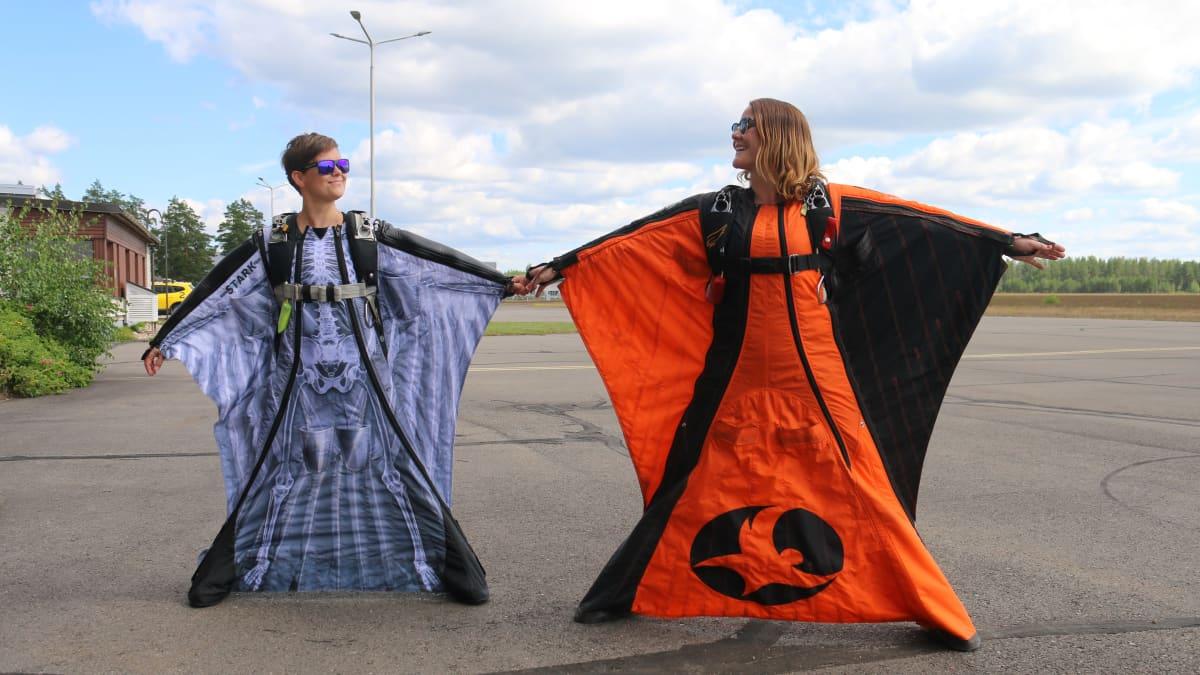Laskuvarjohyppääjät Pilvi Juvonen ja Faye Lawson esittelevät liitopukua Utin lentokentällä