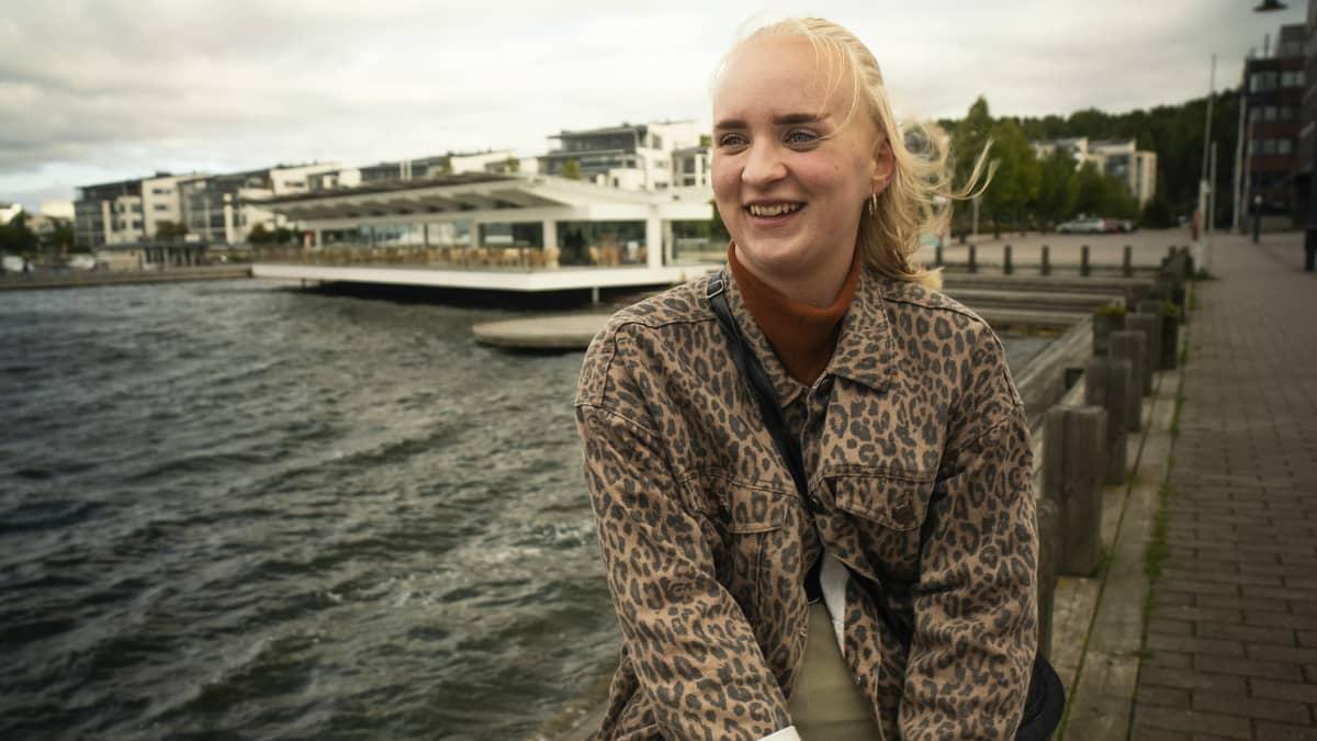 Jasmin Tuomi istuu hymyillen. Taustalla näkyy järven aaltoja ja rakennuksia.