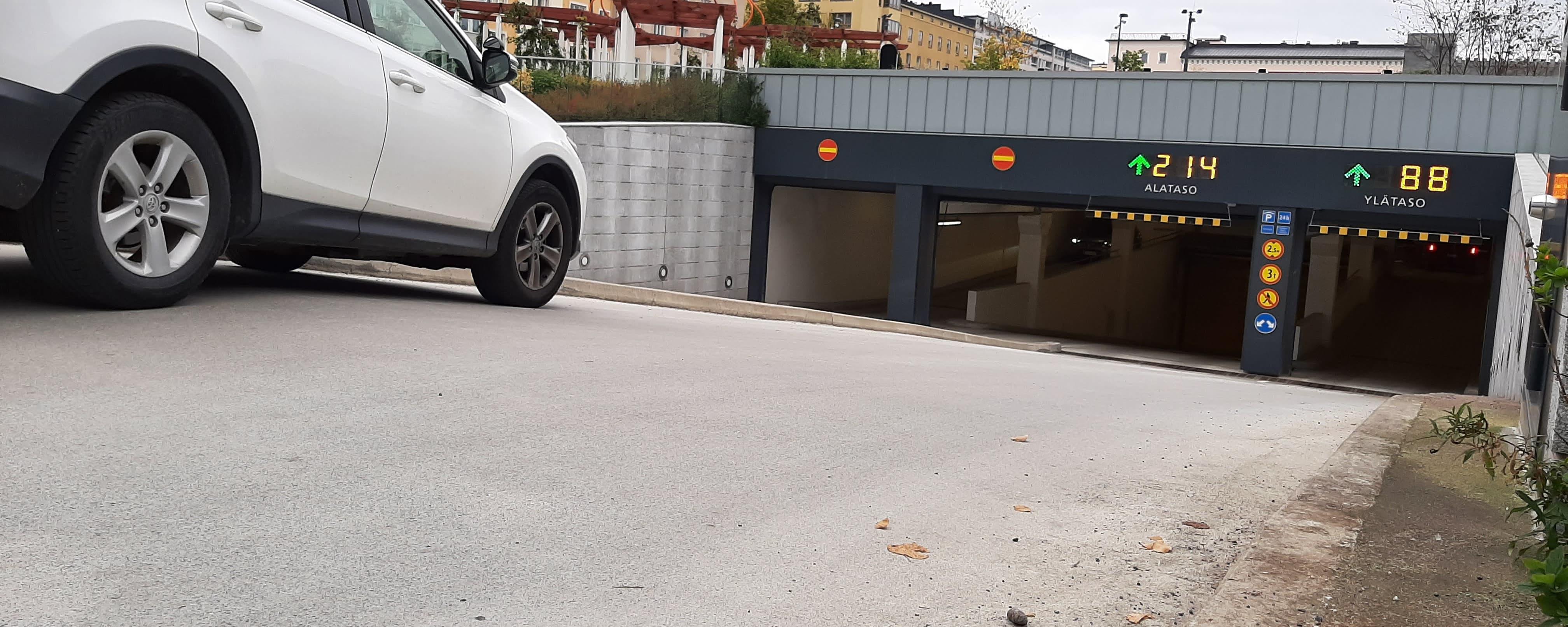 Valkoinen henkilöauto ajaa pysäköintihallin luiskaa pitkin kohti sisäänkäyntejä. Sisäänkäyntien yllä on valokirjaimin ilmoitettu, kuinka monta paikkaa on vapaana.
