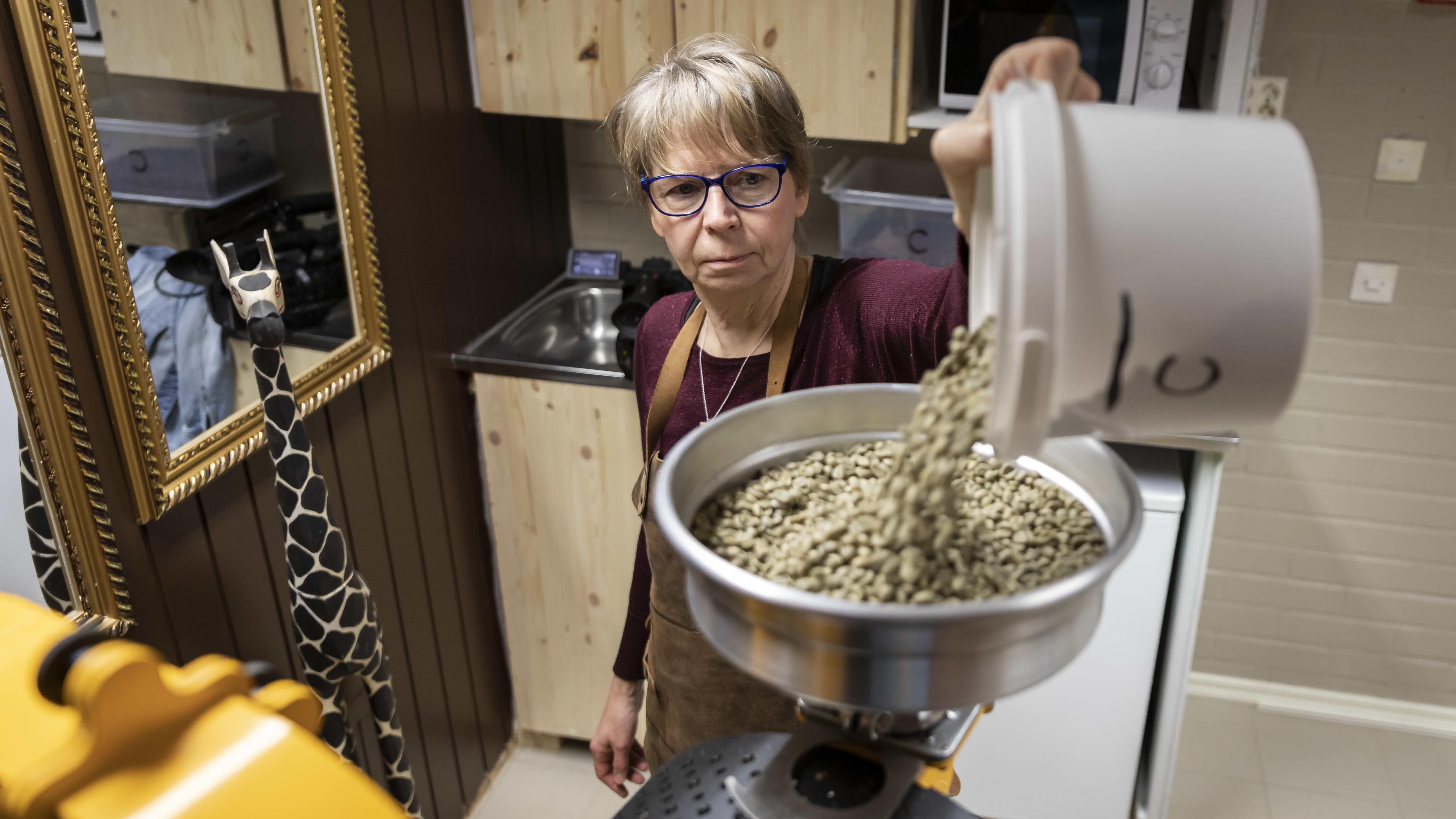 Nainen kaataa kahvipapuja valkoisesta ämpäristä kahvipaahtimeen.