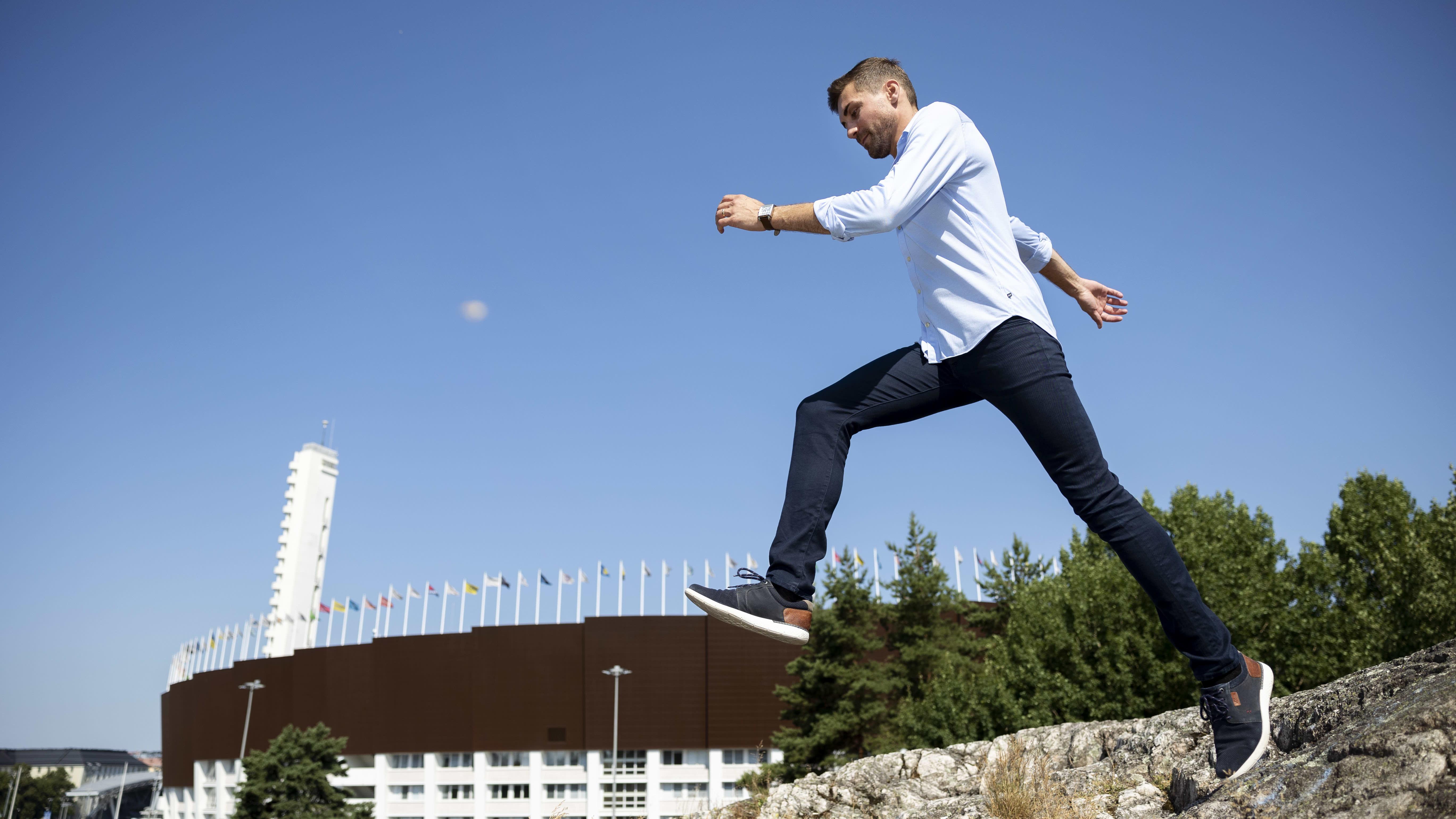 Mies tekee ison loikan kallioilla, miehen takana näkyy Hesingin Olympiastadion ja liehuvat eri maiden liput.