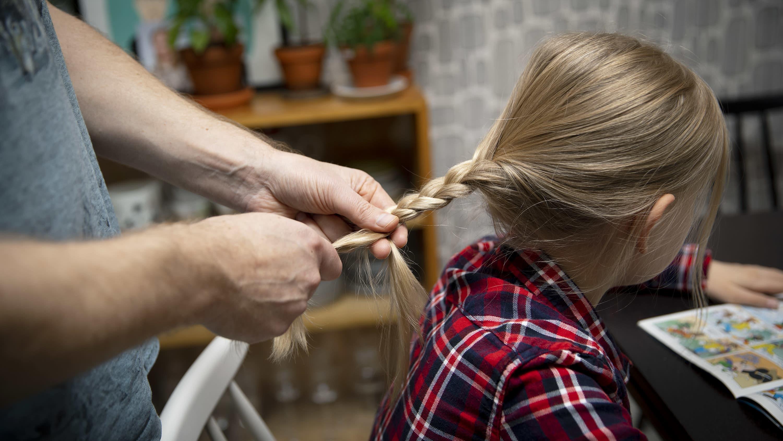 Isä letittää tytön tukkaa