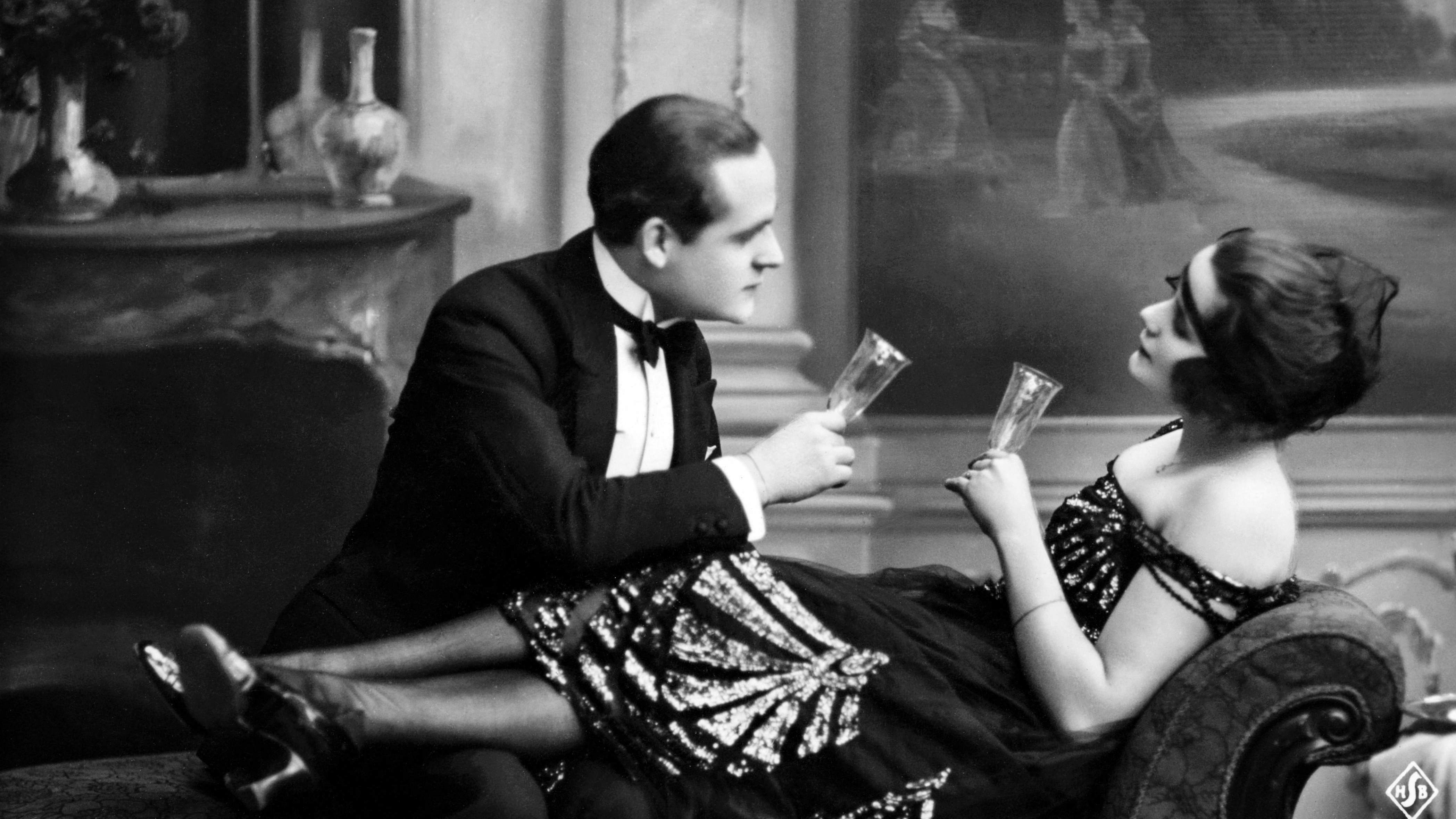 20-lukuinen postikortti, jossa pariskunta siemailee juhlajuomaa divaanilla