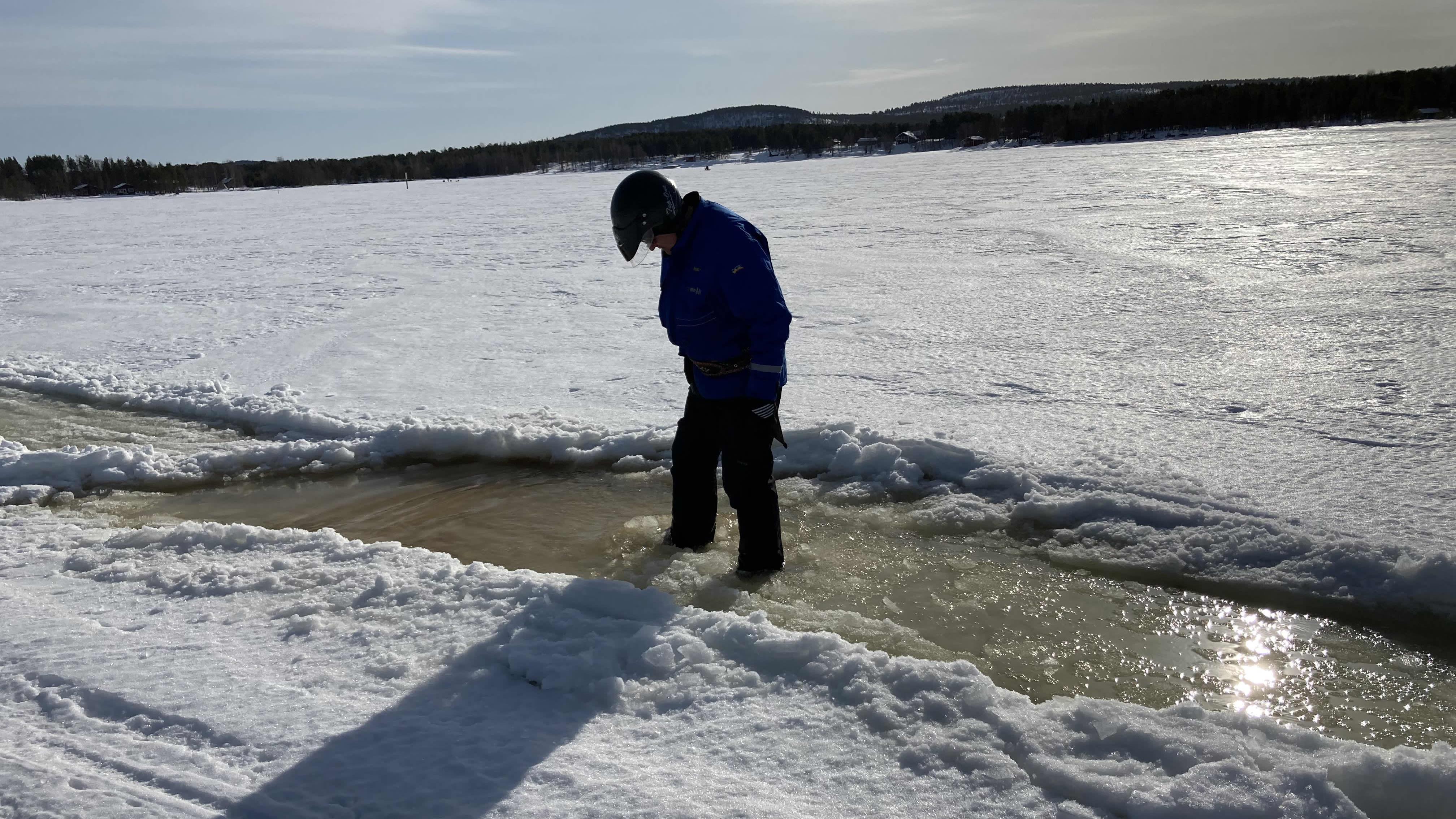Inarijärven jäällä seisoo mies kelkkaurassa, jossa on ainakin 20 senttiä vettä. Aurinko paistaa jäälle.