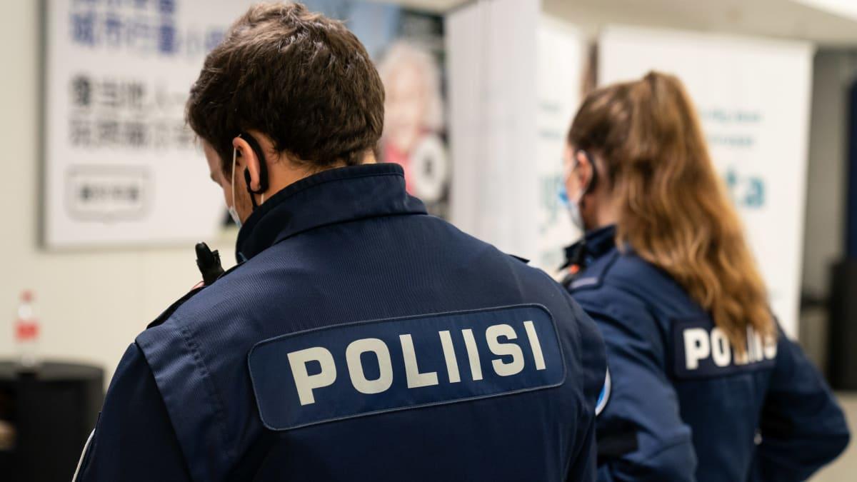 Kaksi poliisia seisoo maskit päässään kuvattuna takaapäin.
