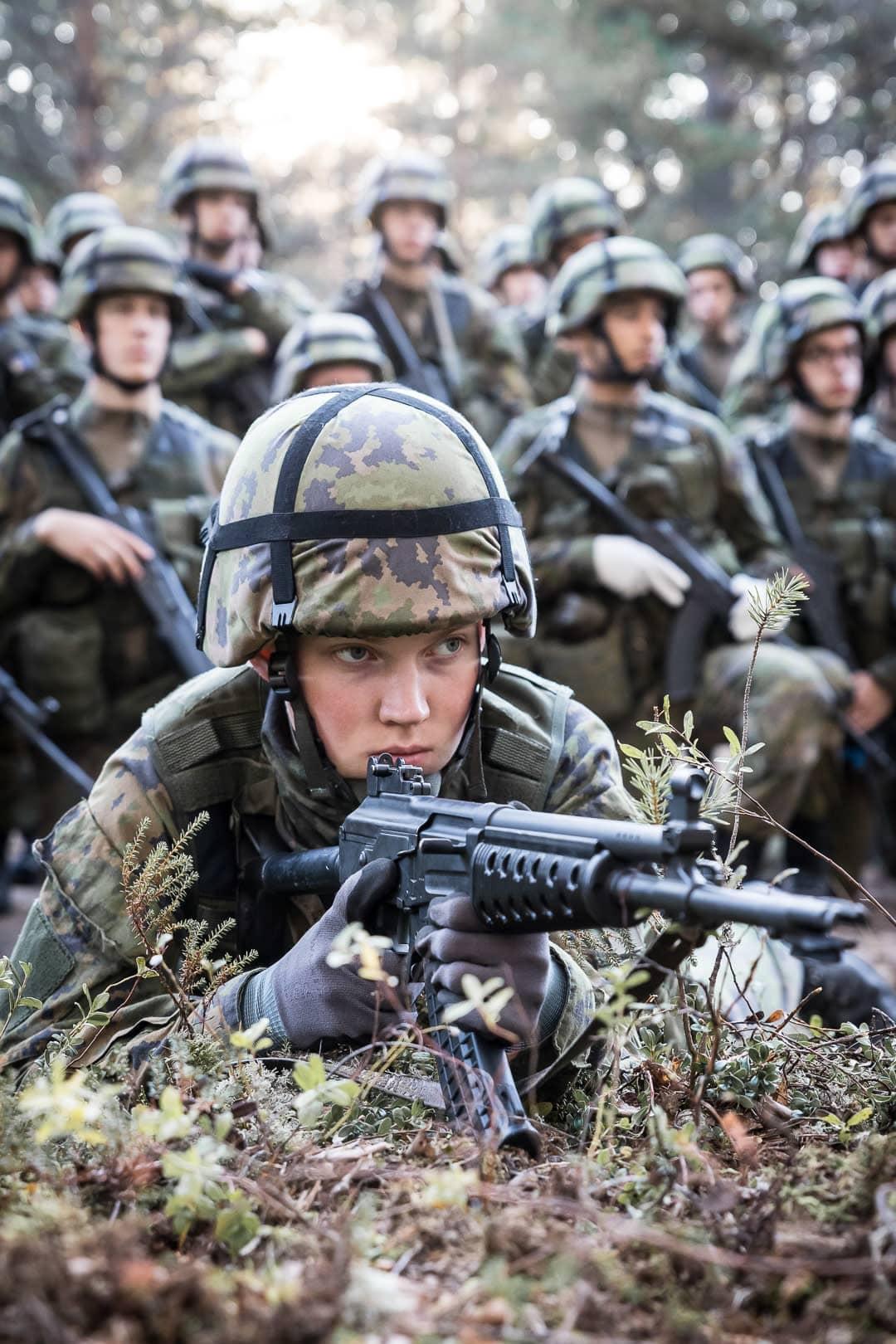 Sotilas nojaa mättääseen rynnäkkökiväärin kanssa.