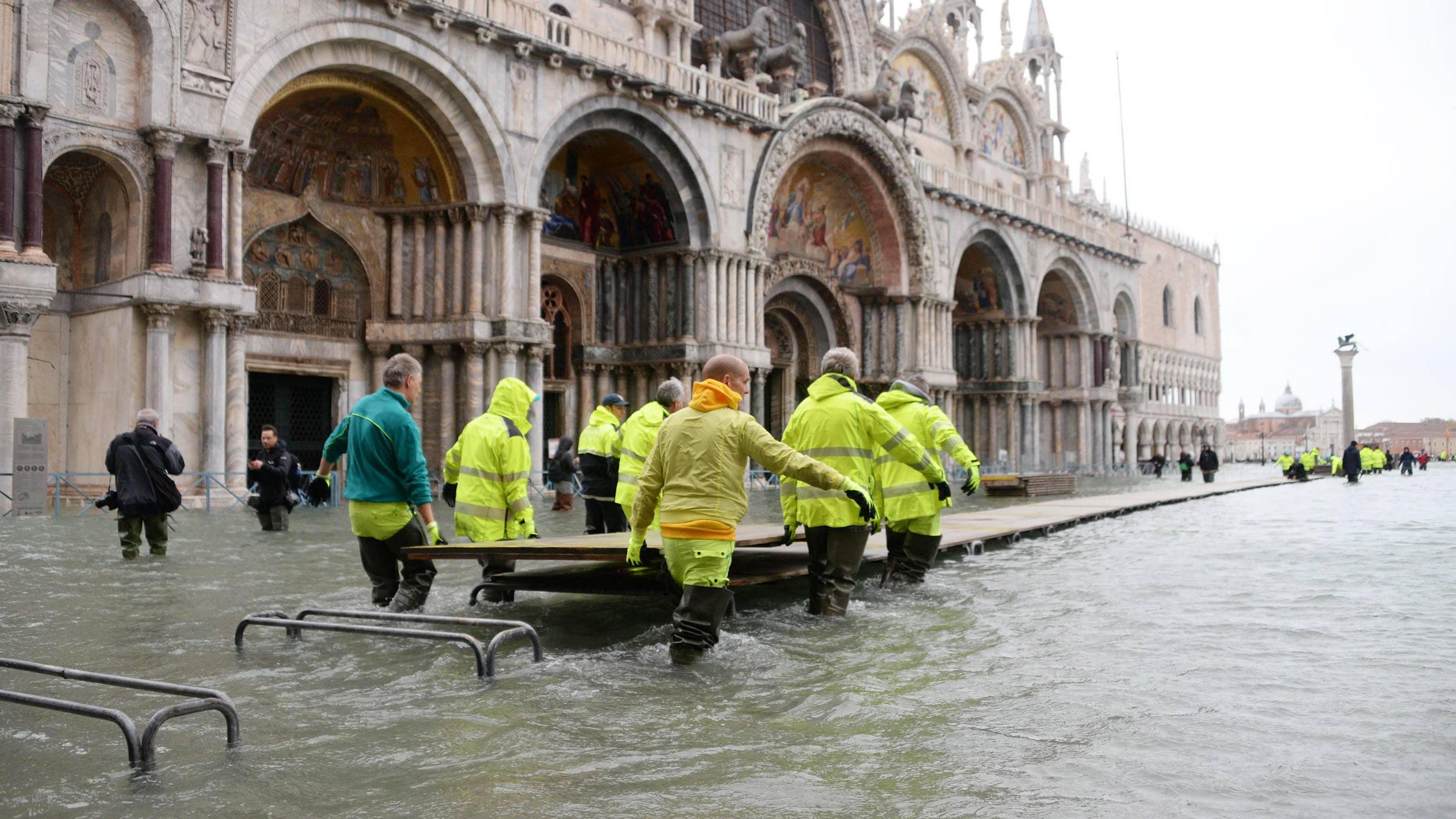 Pelastustyöntekijät kantoivat Pyhän Markuksen torilla siirrettävän sillan palasia.