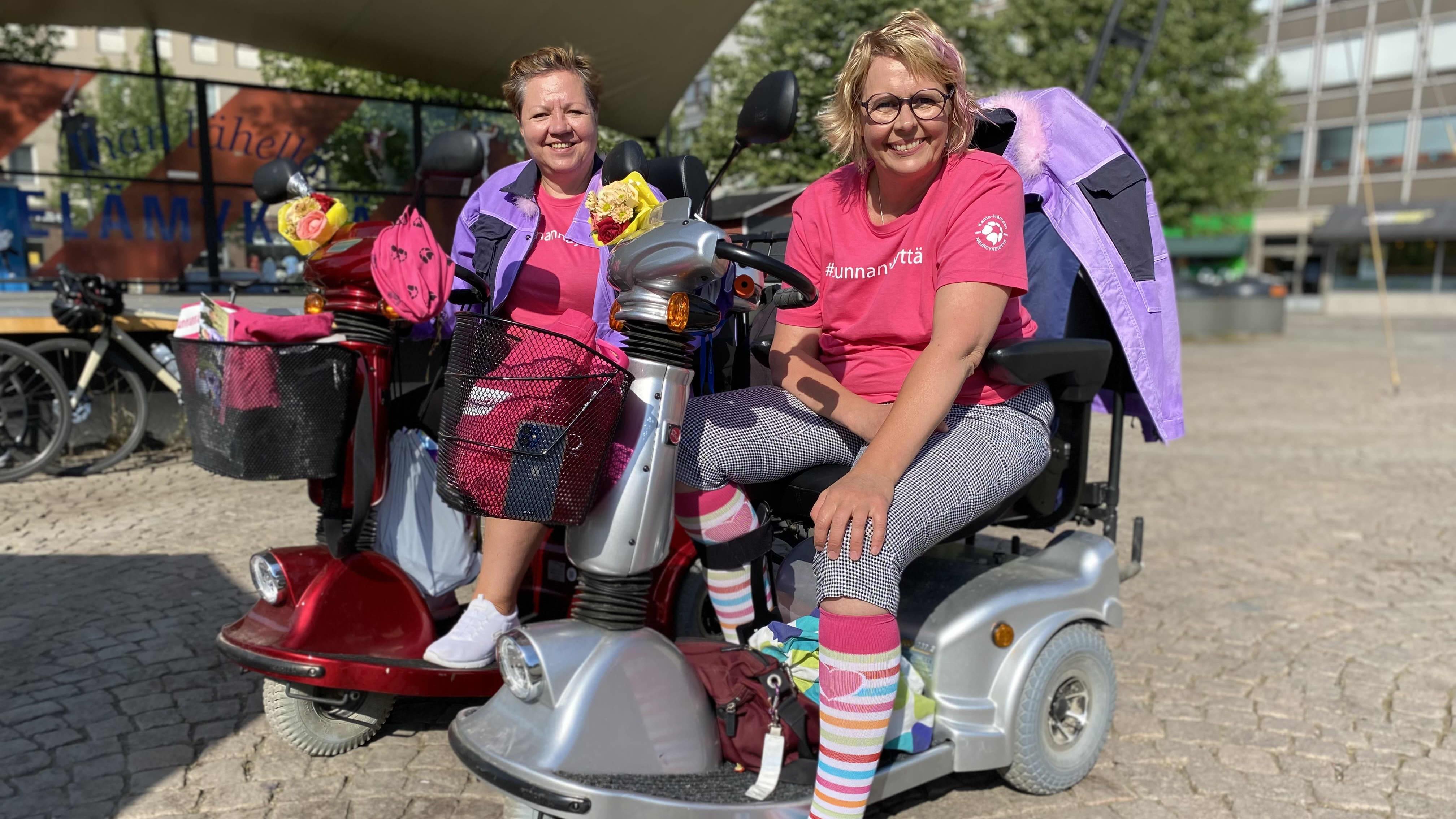 Paula Helin ja PIa-Nina Mohr istuvat sähkömopoissaan aurinkoisella Hämeenlinnan torilla