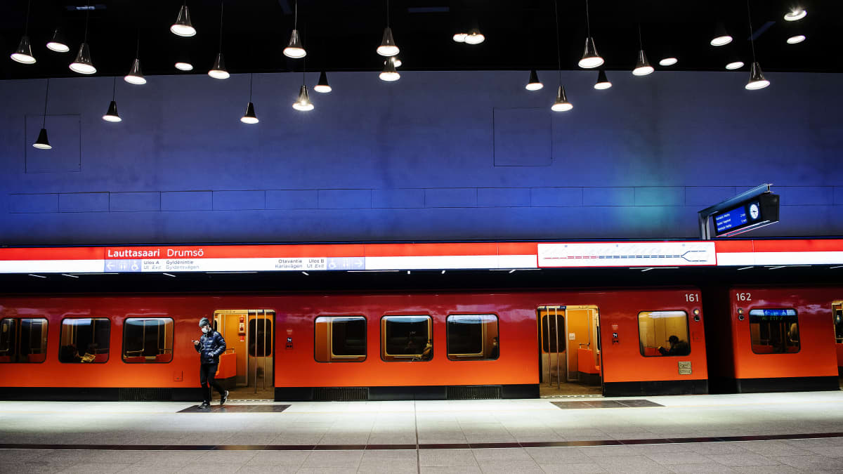 Henkilö astuu ulos metrosta Lauttasaaren metroasemalla.