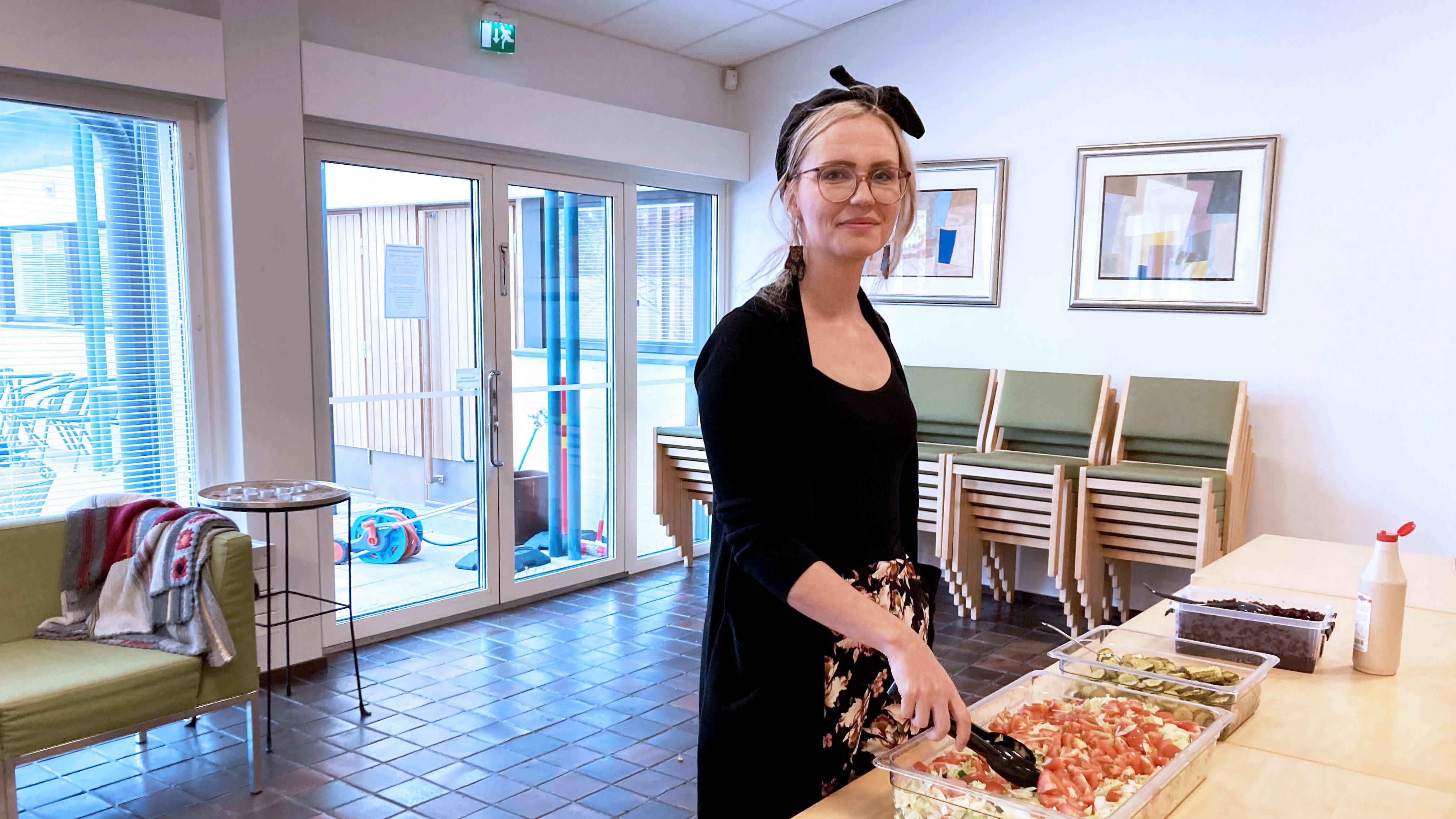 Diakoni Suvi Kervinen Kotka-Kymin seurakunnasta katsoo kameraan samalla, kun sekoittaa salaattia Karhulan seurakuntakeskuksella pöydän ääressä.