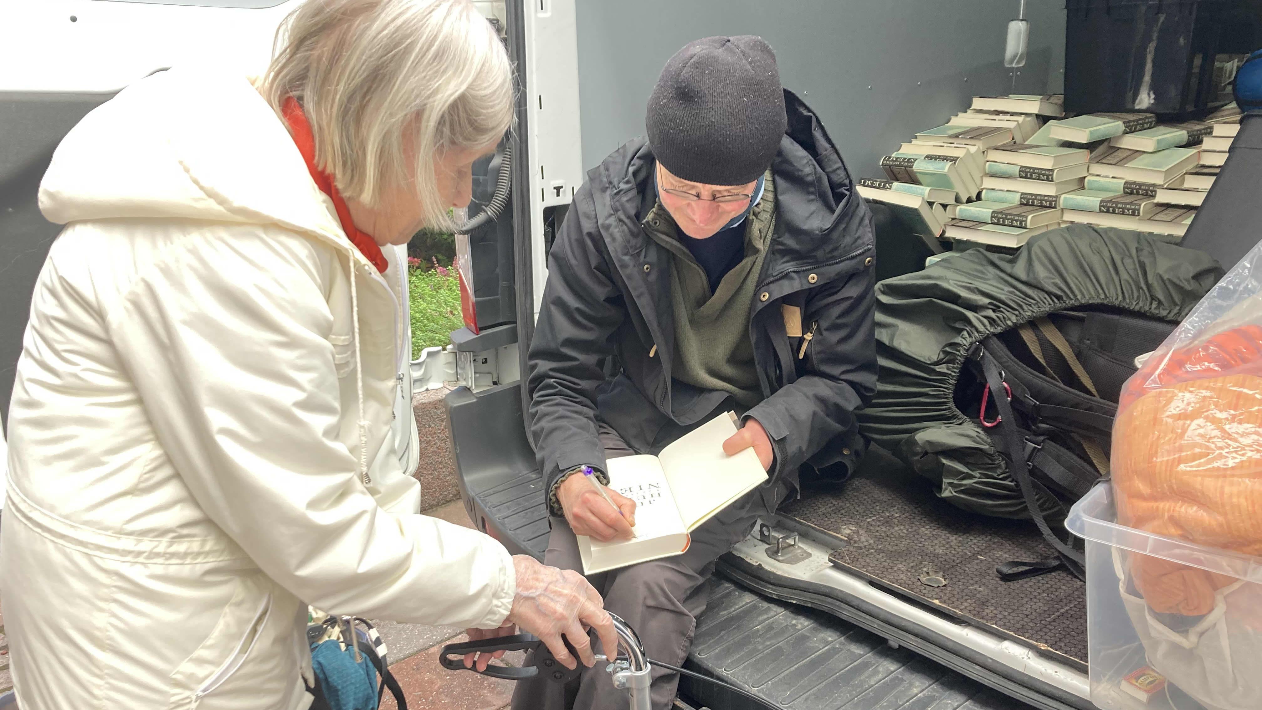 Juha Hurme signeeraa Niemi-teostaan fanille istuen pakettiautossa.