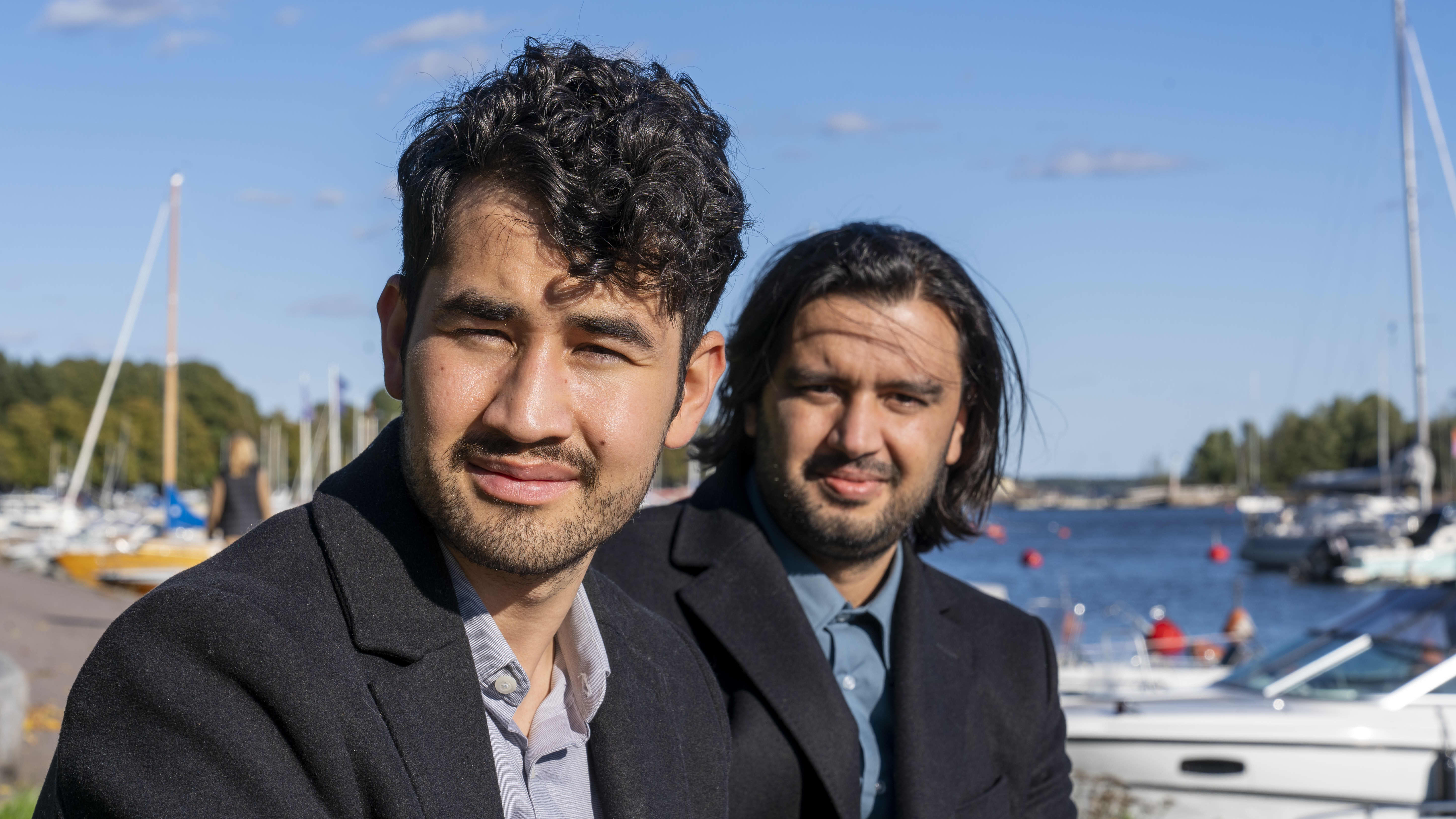 Afganistanilainen Mojtaba Qanzadeh, opiskelija ja Ershad Noorzai, filosofi, istuvat kaivarin rannassa, taustalla purjeveneet