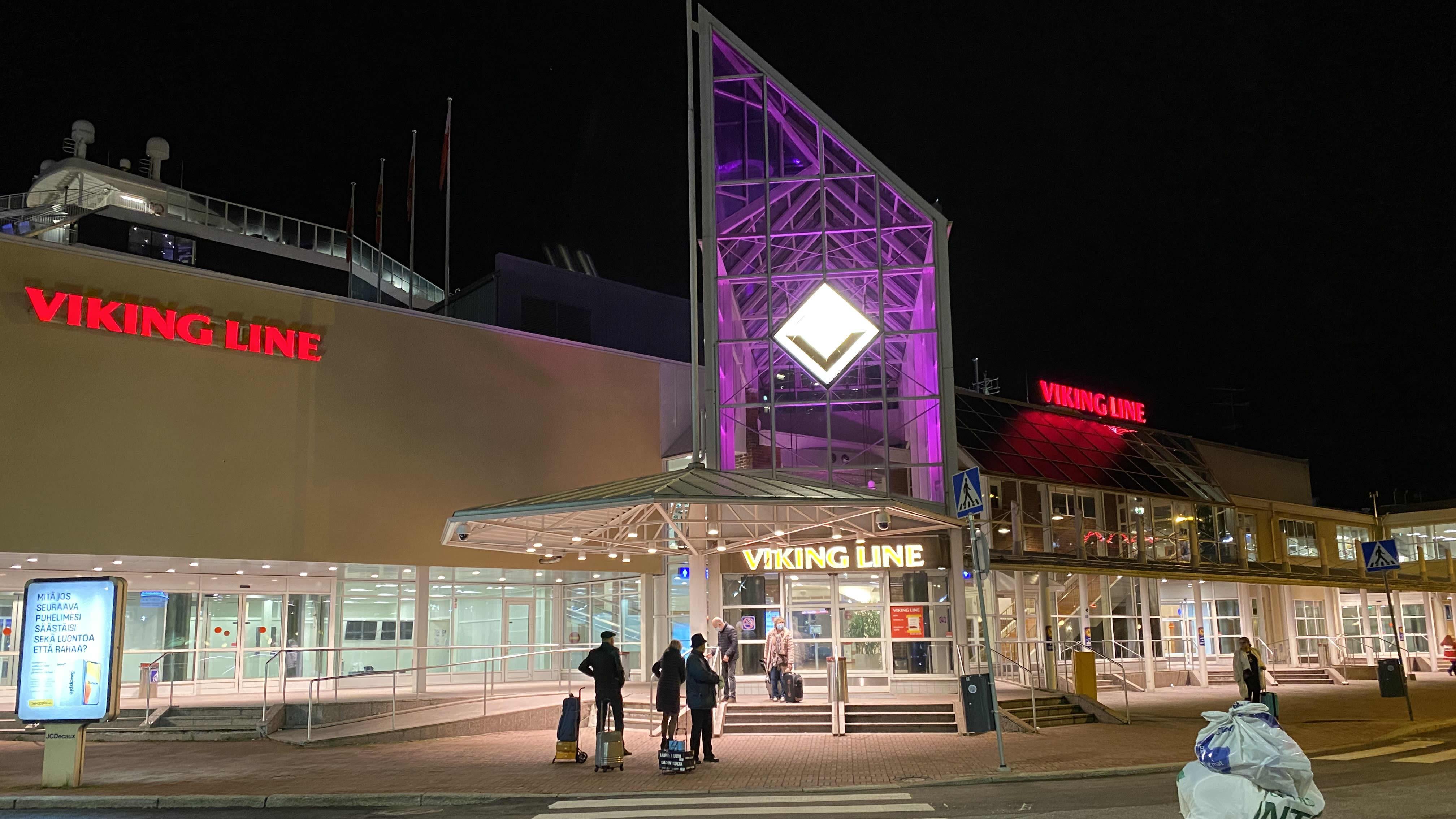 Muutamia ihmisiä seisoo Turun satamassa Viking Linen terminaalin edessä.