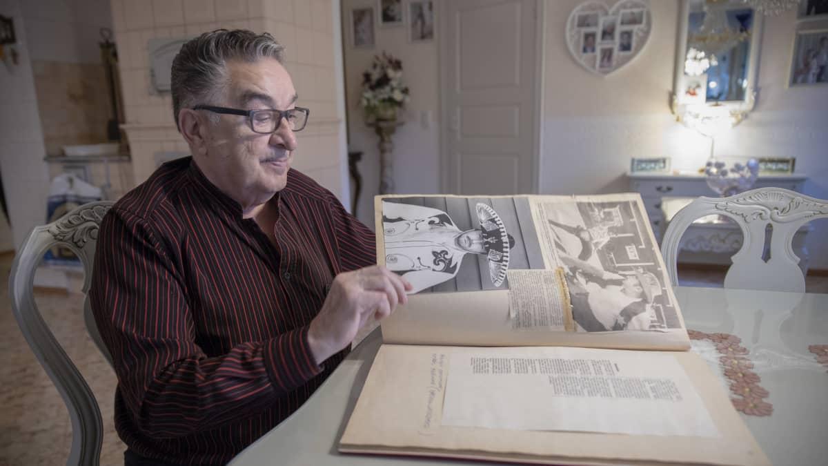 Rainer Roth selaa leikekirjaa kotonaan