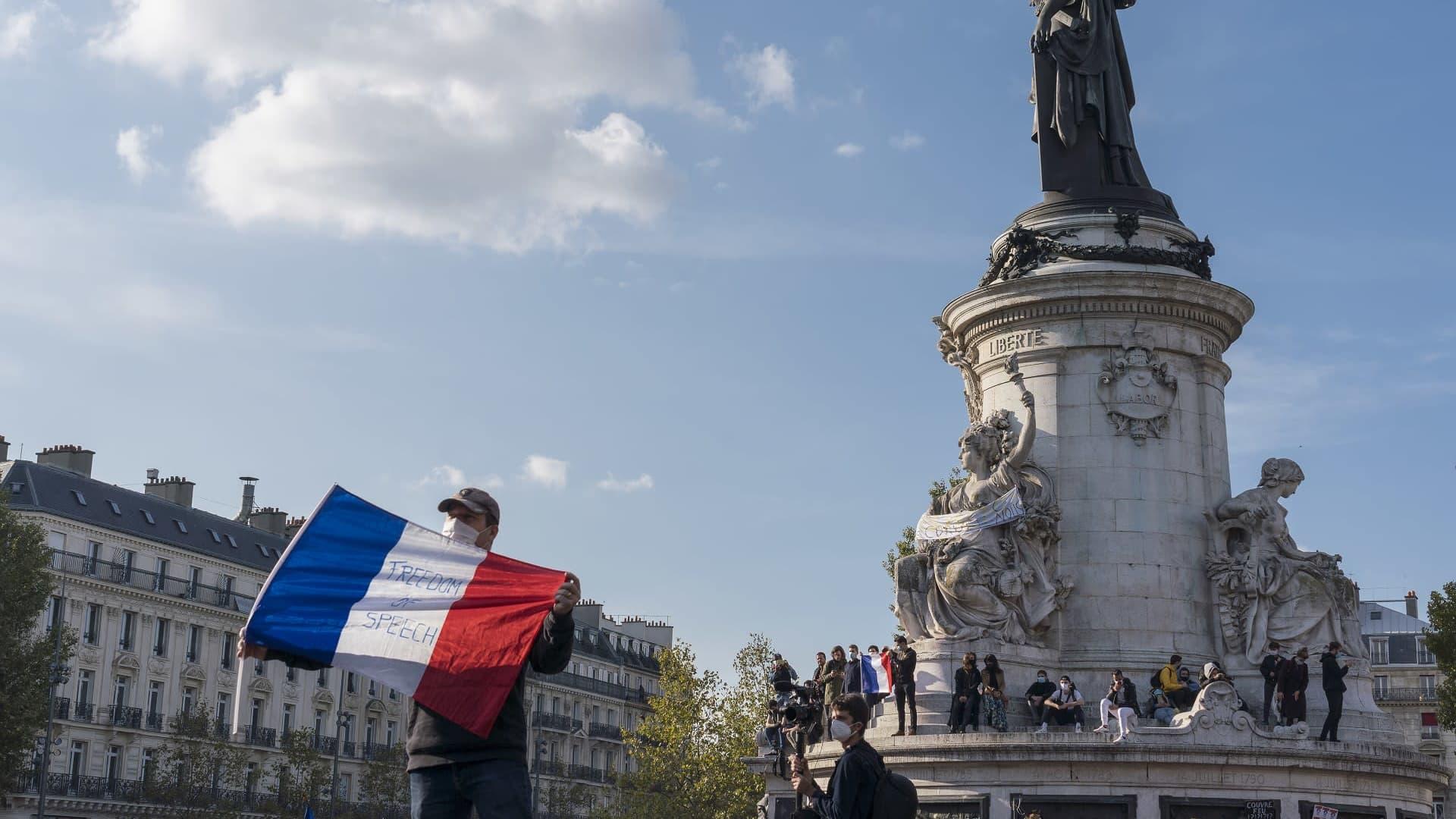 Mies pitelee Ranskan lippua aukiolle, jossa on myös paljon muita ihmisiä.