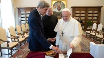 John Kerry osoittaa kirjan sivua paaville.