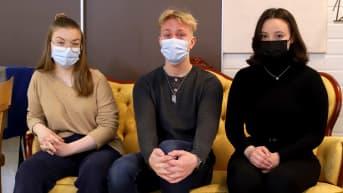Sara Mäkinen, Miro Taimen ja Wendi Kivistö istuvat sohvalla maskit kasvoillaan jat katsovat kameraa kohti