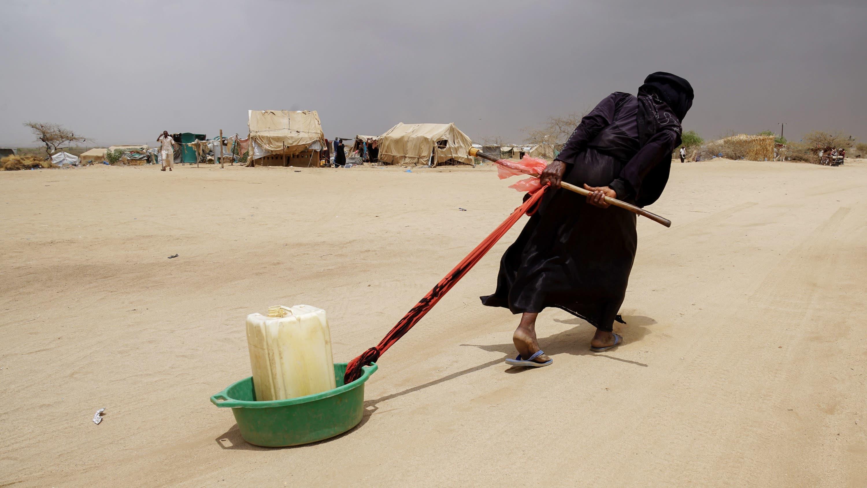 Nainen vetää vesikanisteria perässään.