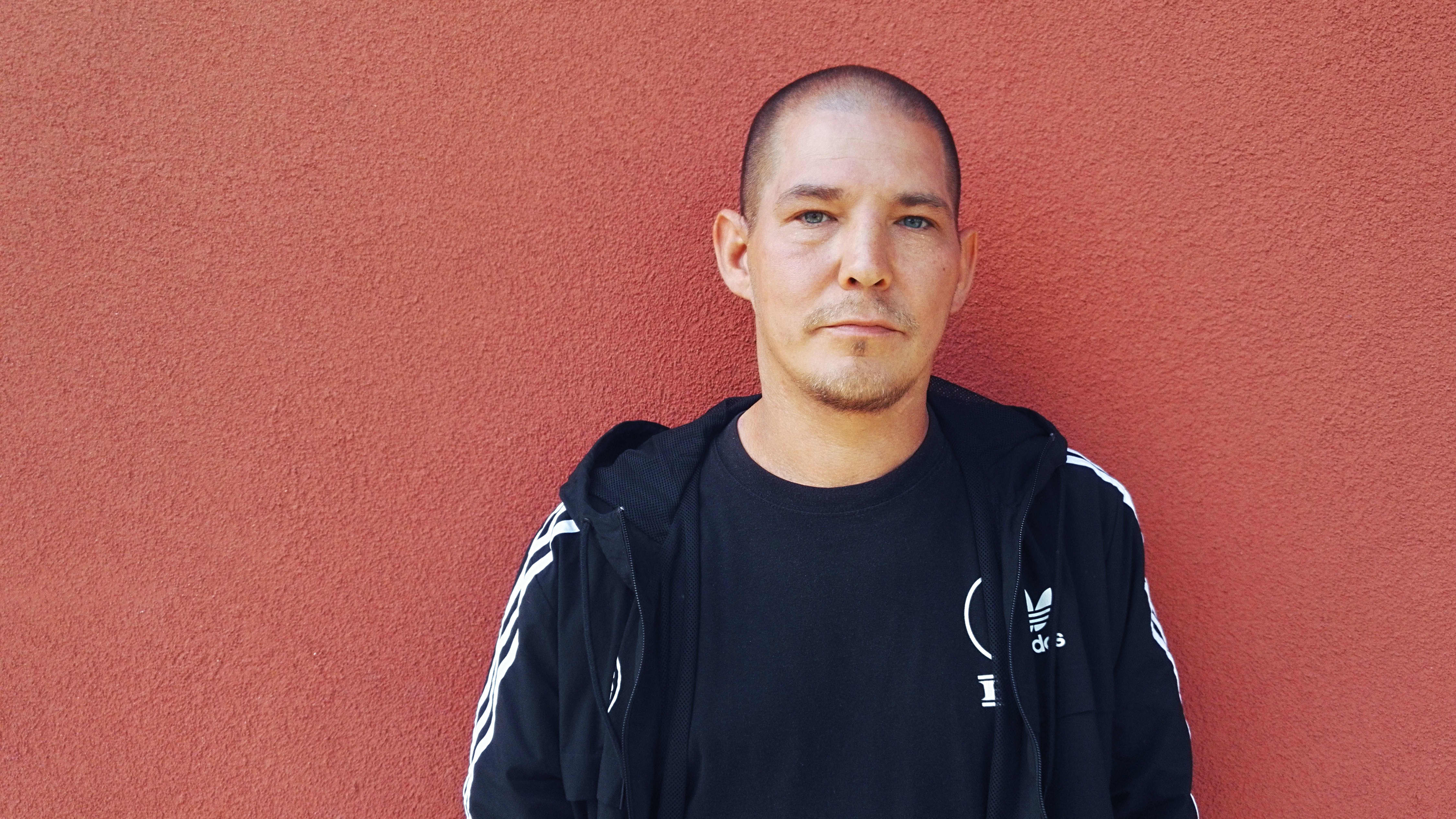 Jalmari Helander seisoo punaisen rapatun seinän edessä ja katsoo kameraan.