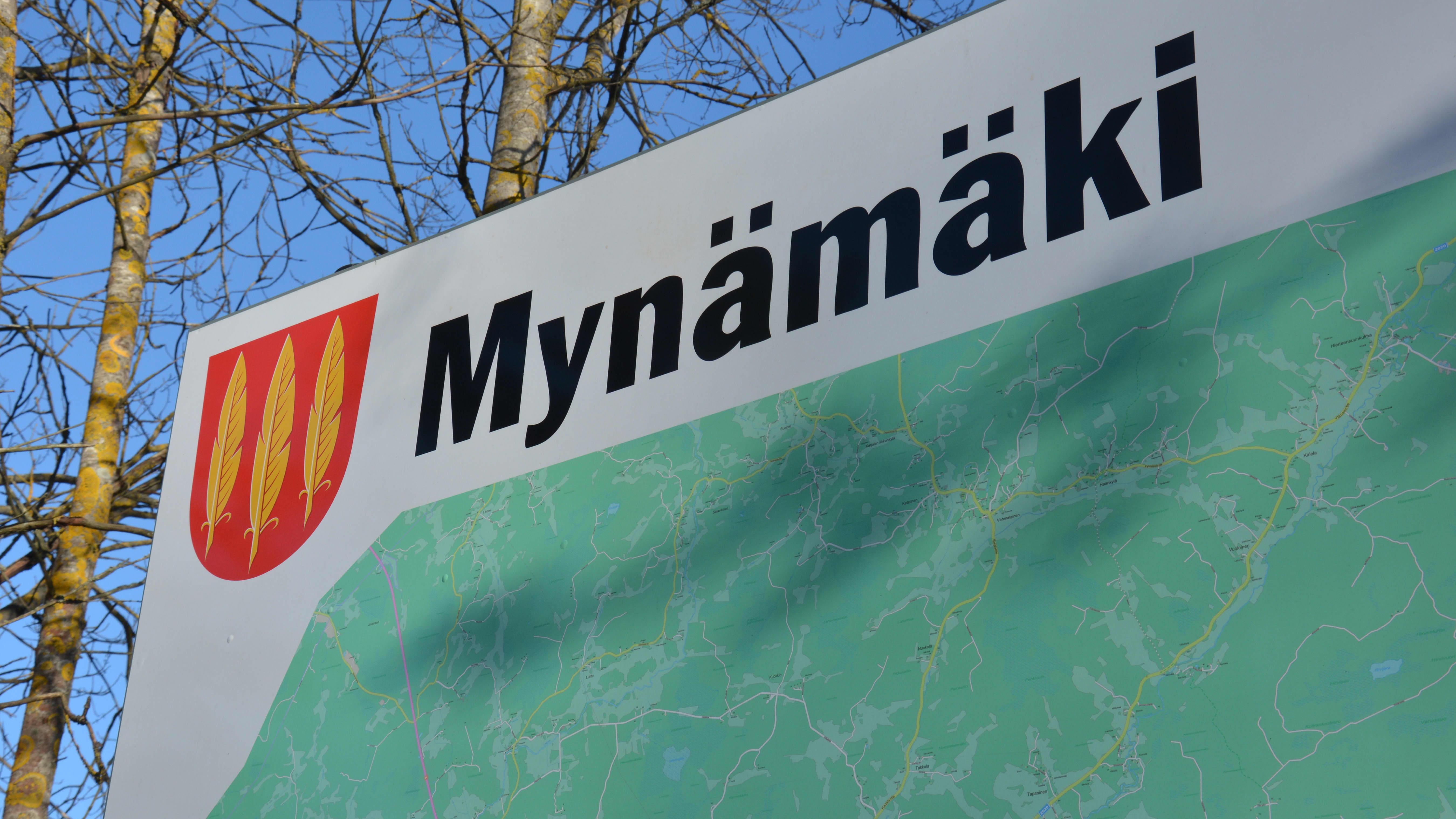 Mynämäki-kuntakyltti maastossa.