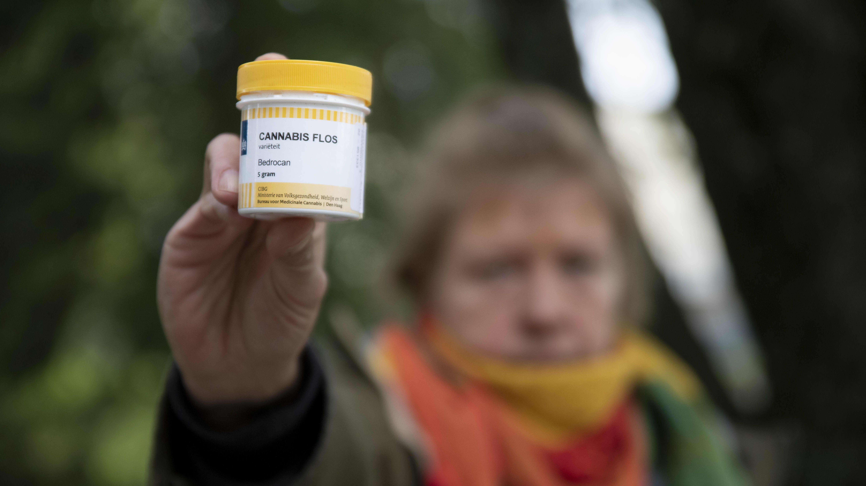 Nainen pitää lääkekannabispurkkia kädessään.
