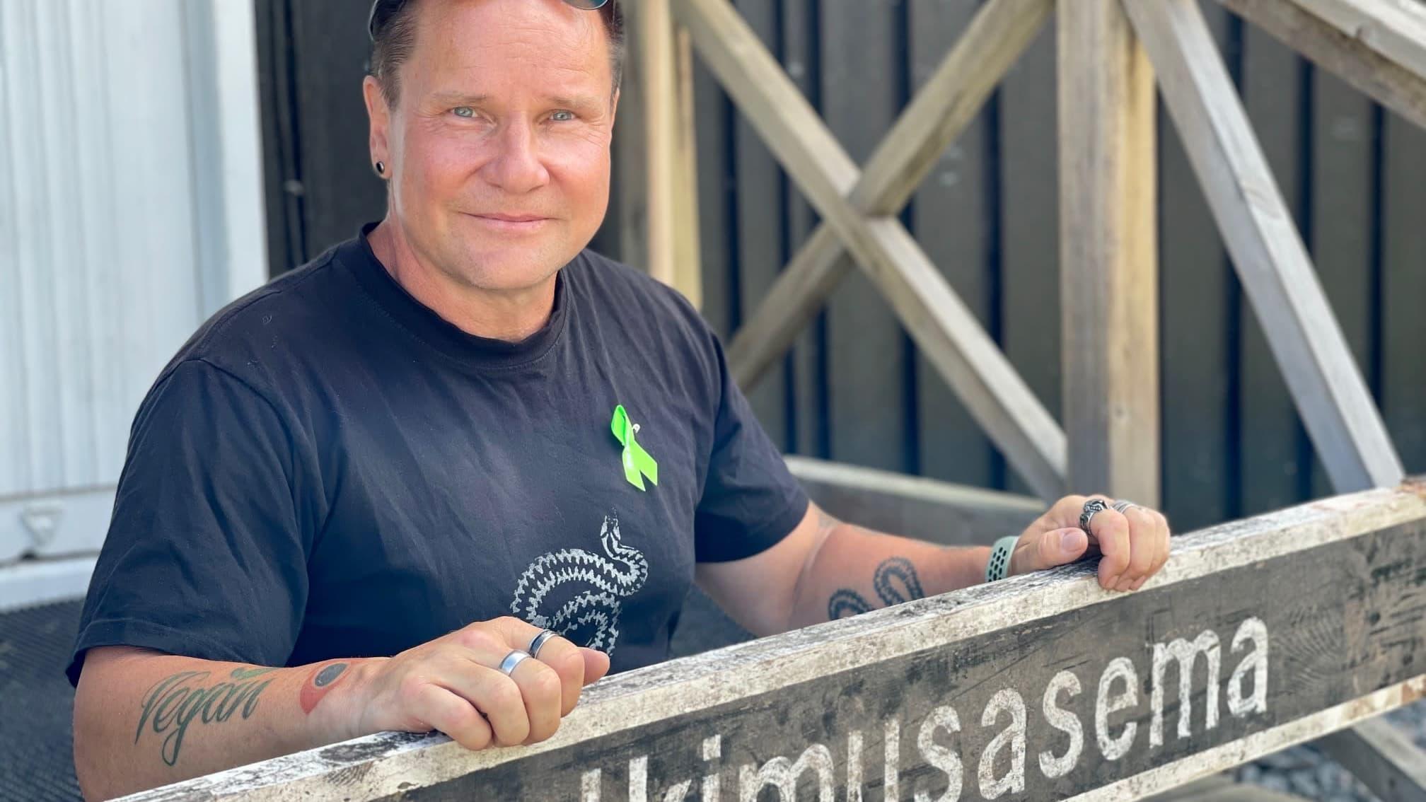 Mies istuu puurakennuksen portailla sylissään iso puinen kyltti, jossa lukee tutkimusasema
