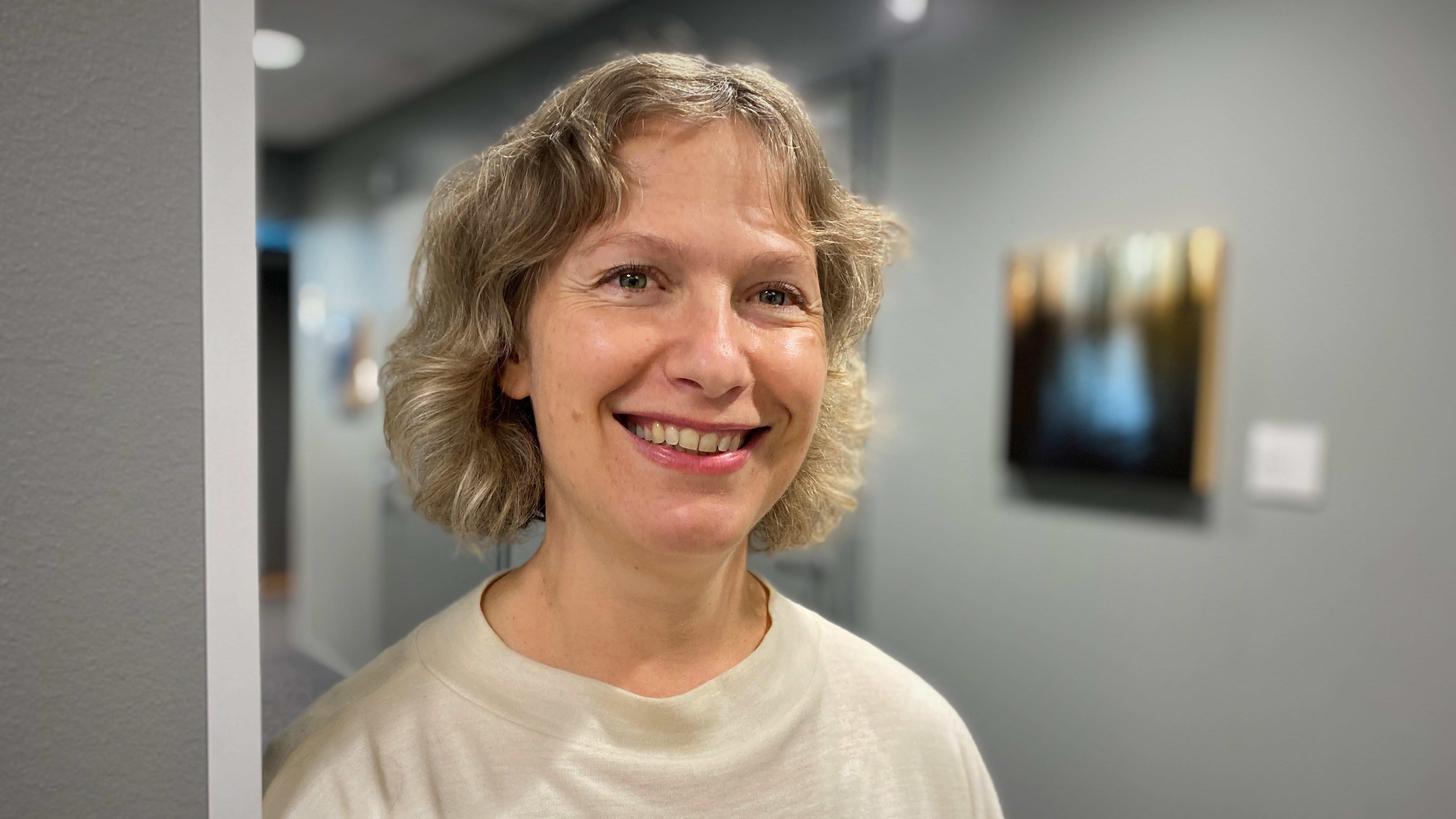 Vaaleahiuksinen ja valkopaitainen nainen hymyilee kameralle toimiston käytävällä.