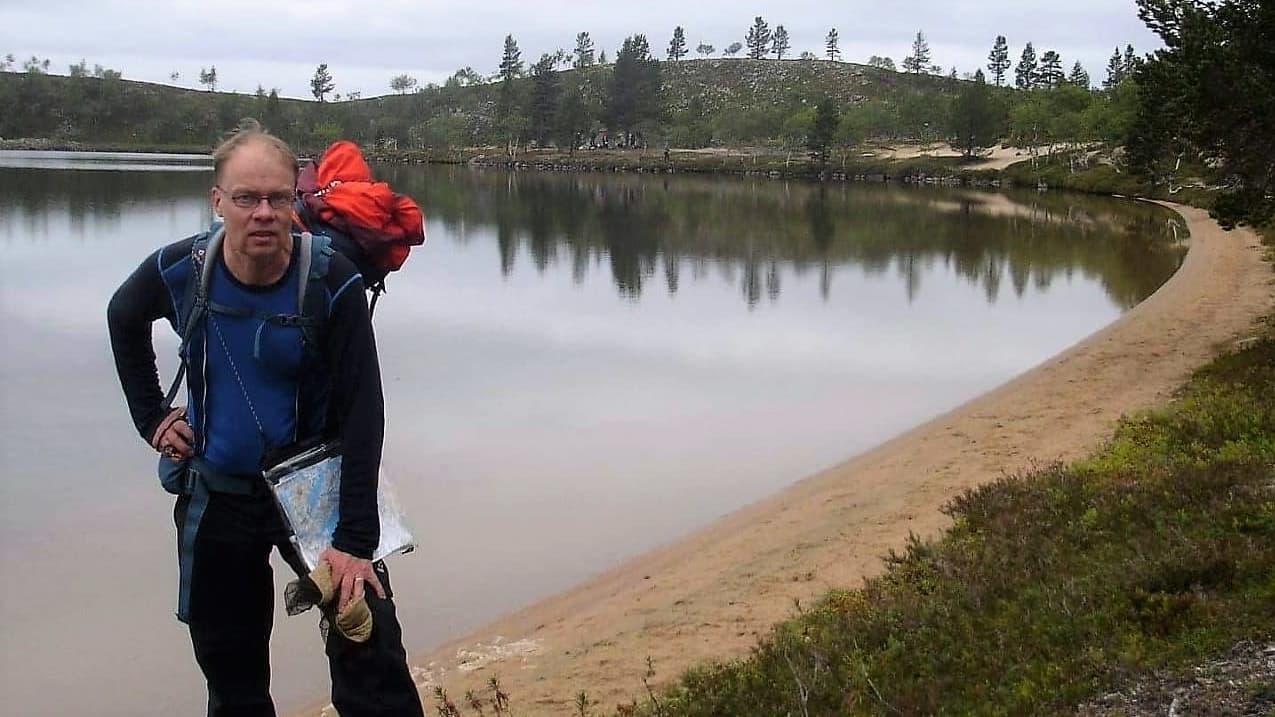 Vesa Koivunen retkellä kartta kädessä järven rannalla