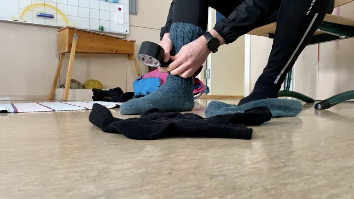 Mies pukee villasukkaa jalkaan