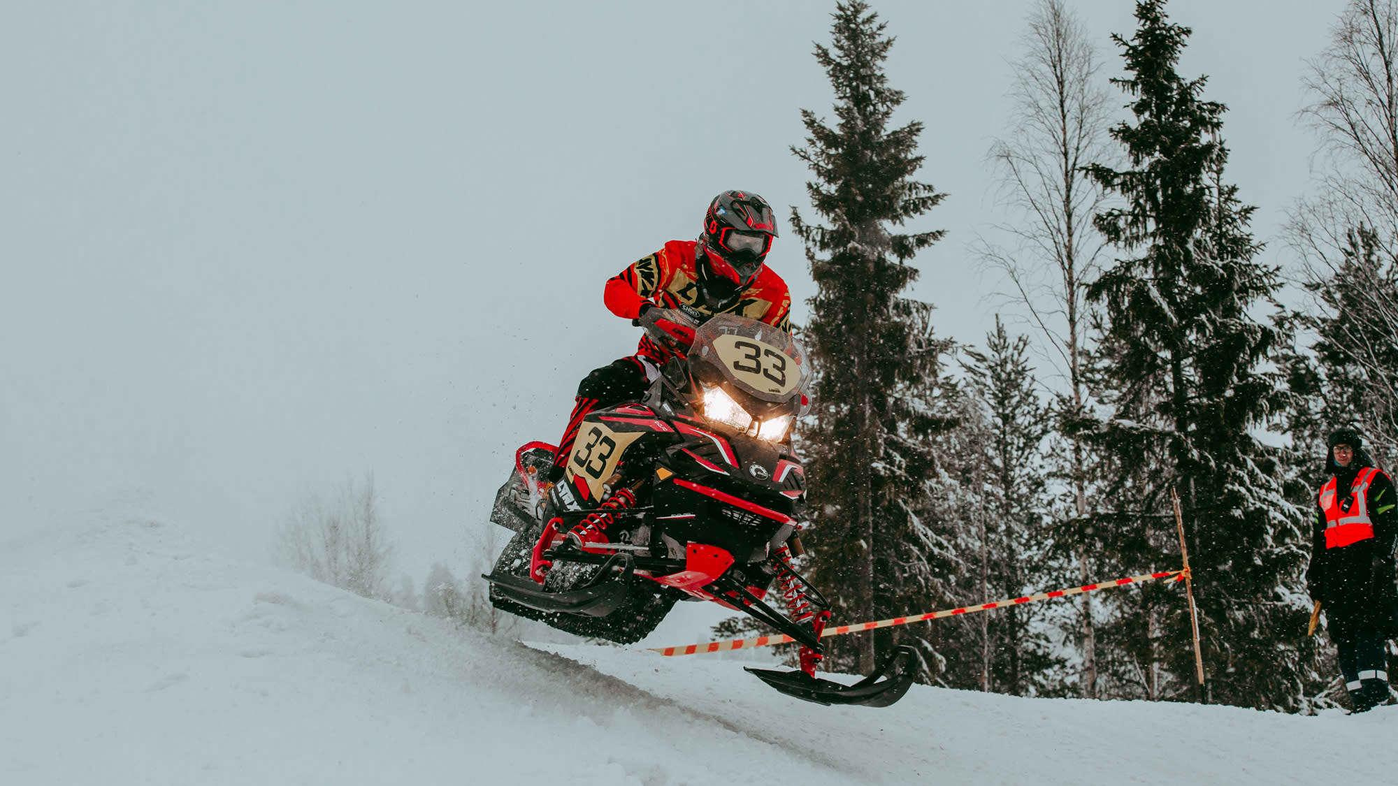 Moottorikelkka kiitää lujaa lähes ilmassa lumisessa metsässä