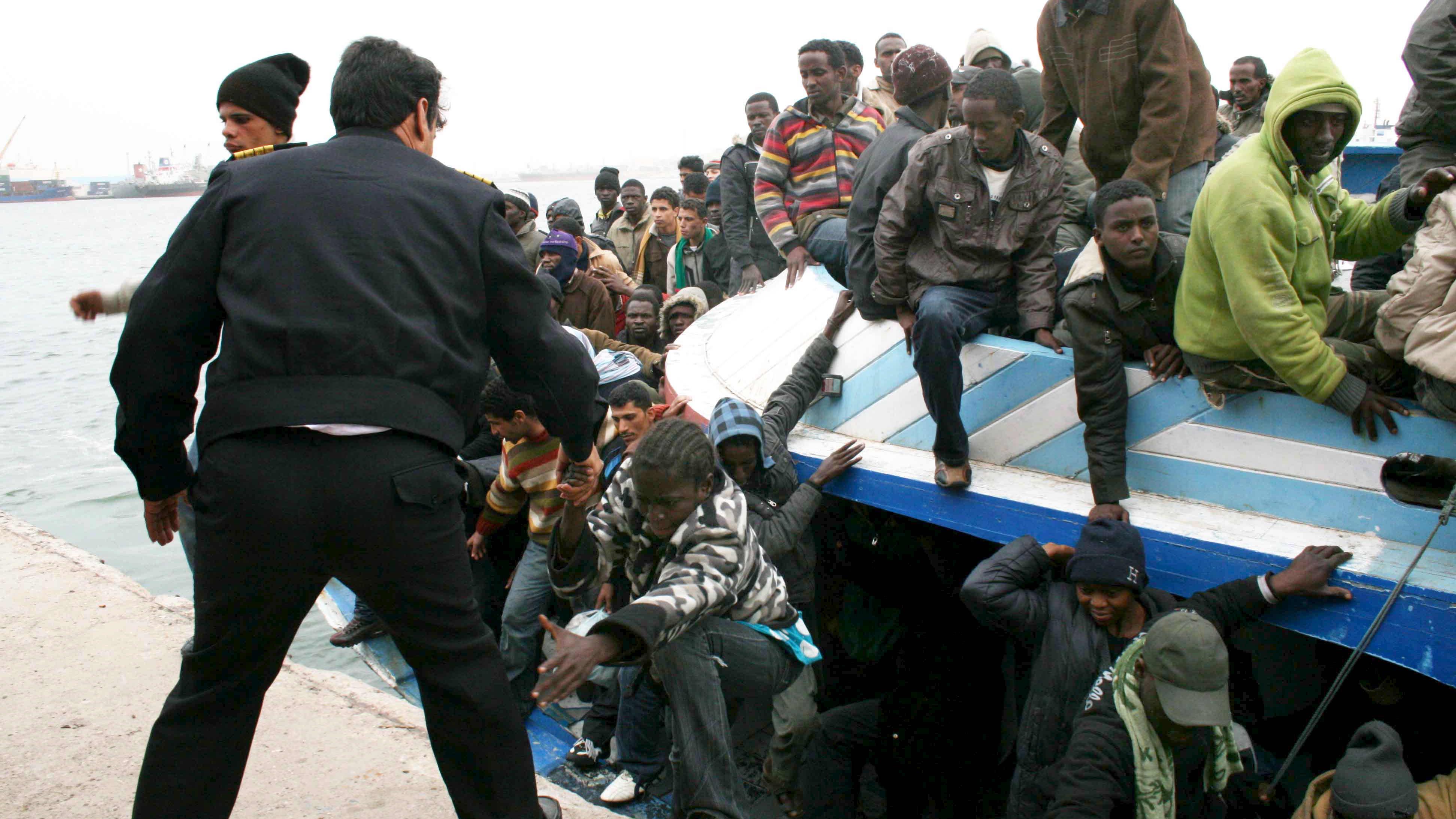 Libyan poliisi auttaa siirtolaisia ulos täyteen ihmisiä ahdetusta veneestä Tripolissa.
