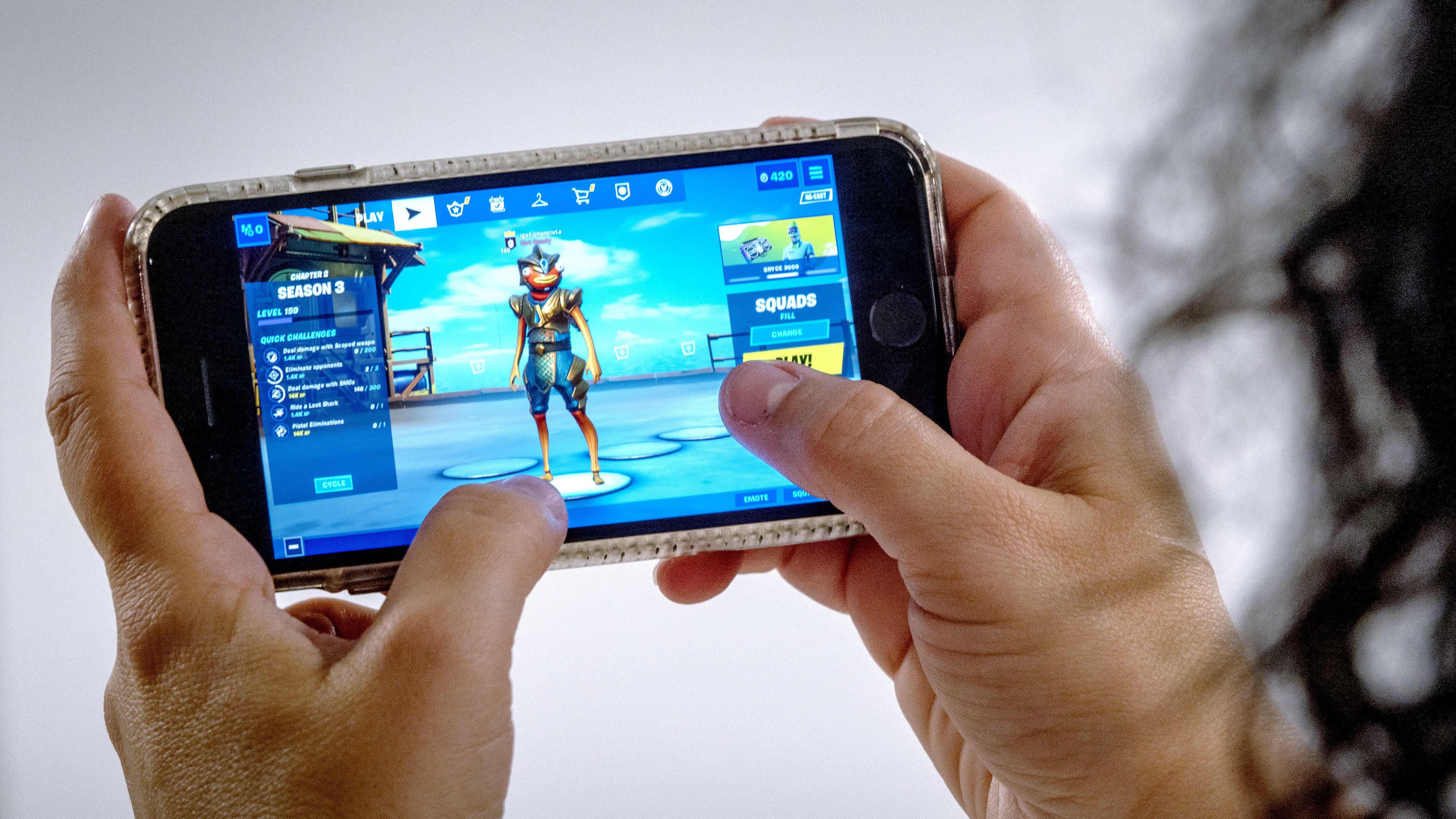 Henkilö pelaa Fortnite-peliä puhelimella